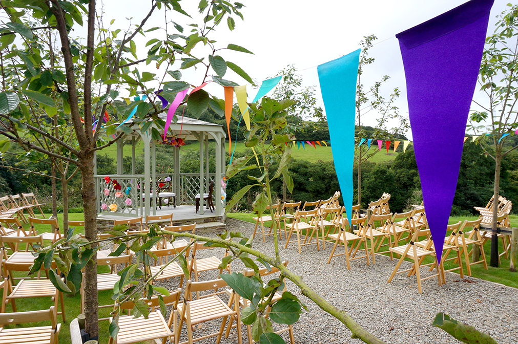 Bright colour pop outdoor wedding ceremony at wedding venue Pengenna Manor in Cornwall.jpg