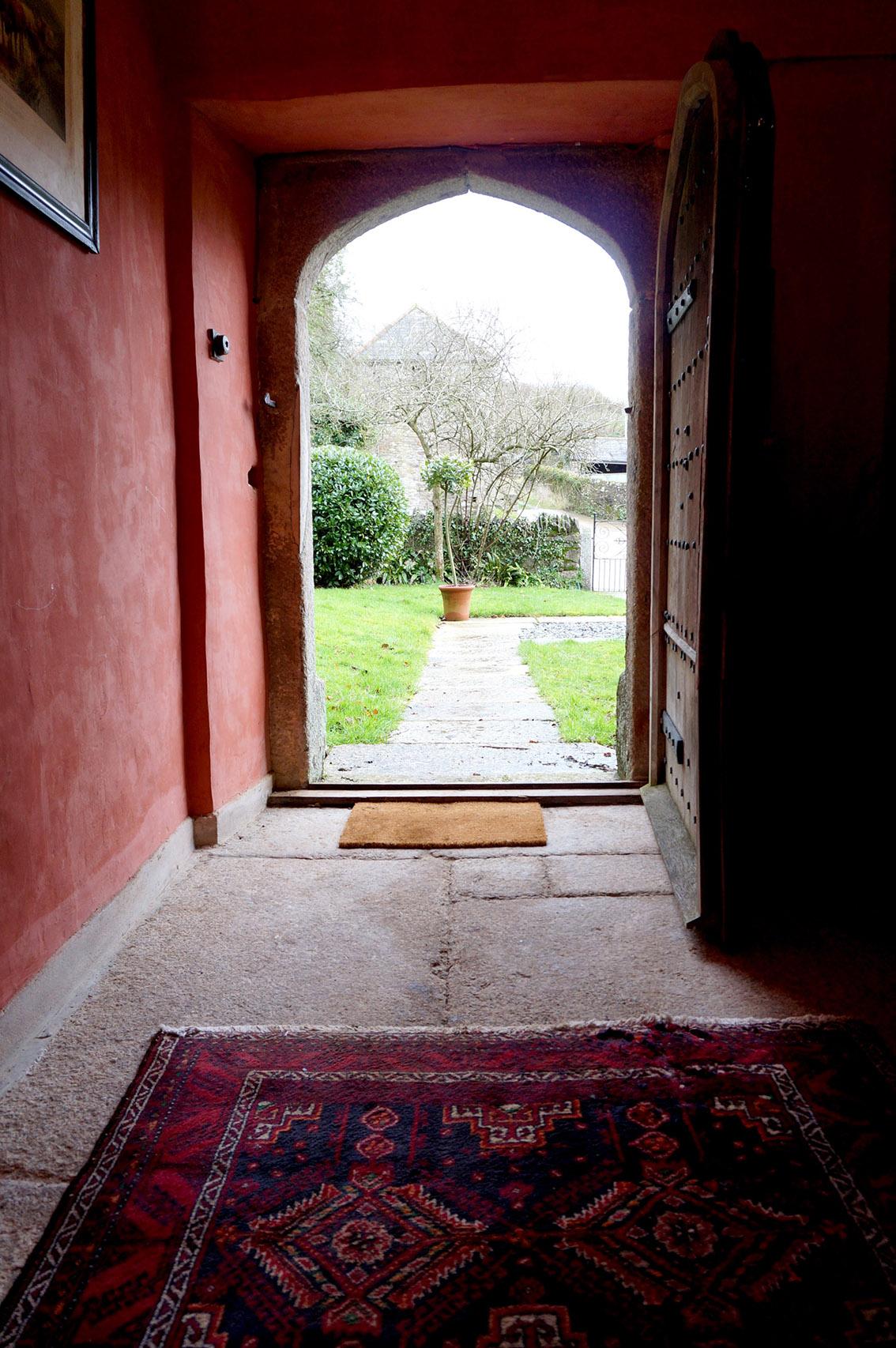 Outdoor wedding ceremonies under the arch of the front door of Cornwall wedding venue Pengenna Manor.jpg
