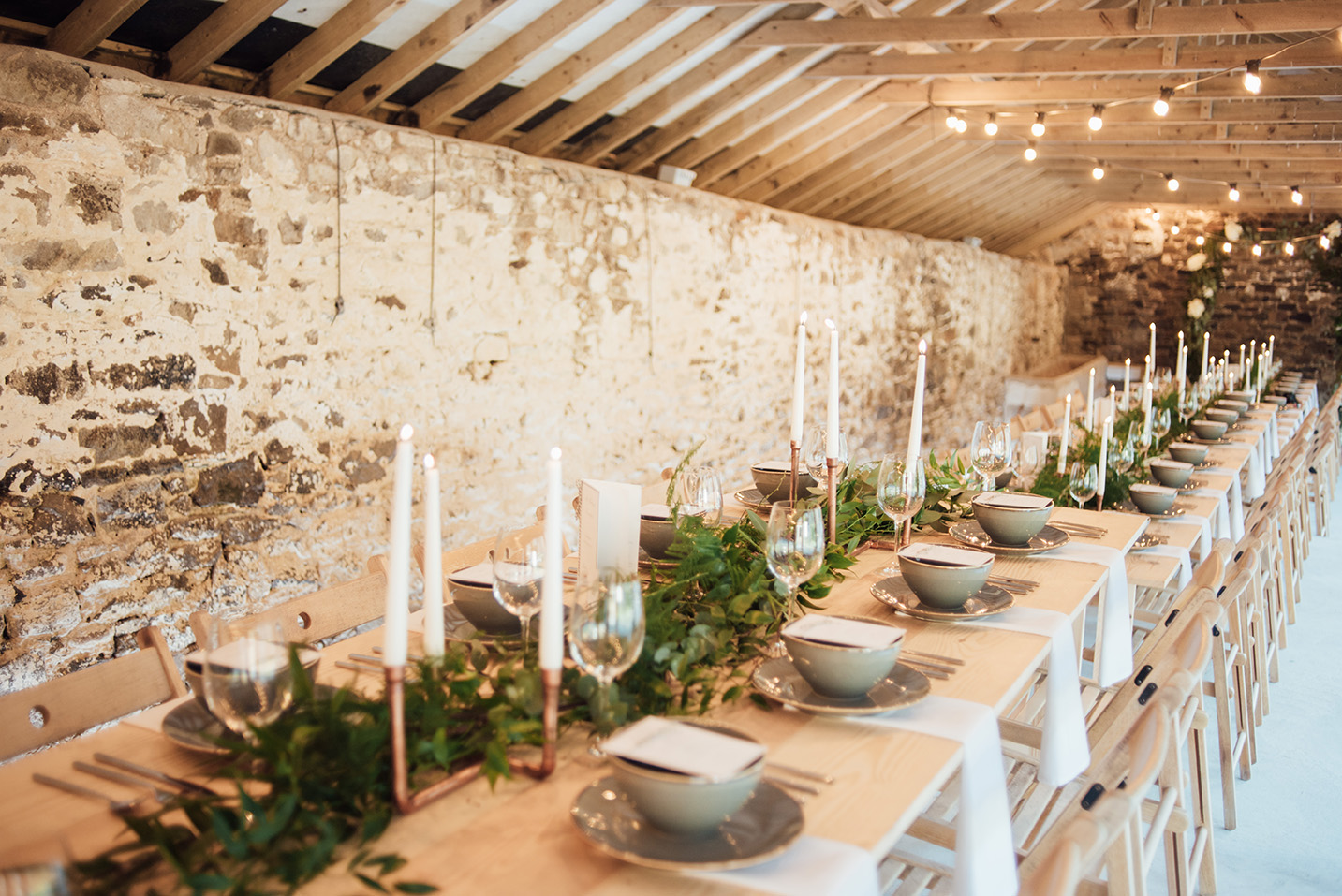 The inside of the Cowyard Barn rustic party and reception space set for an evening dinner at Pengenna Manor Cornwall wedding venue03.jpg