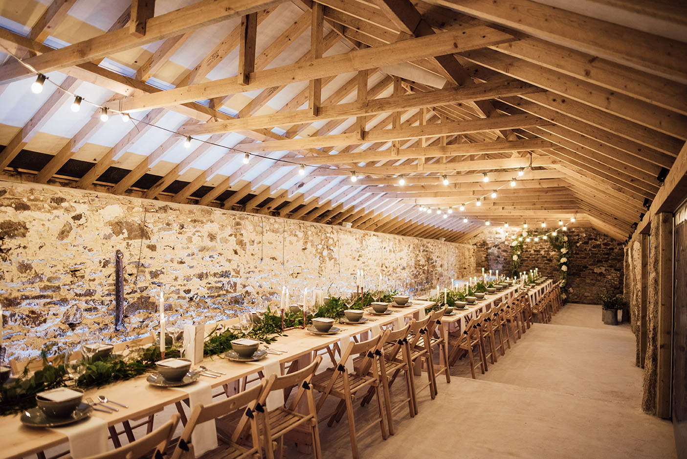 The inside of the Cowyard Barn rustic party and reception space set for a night time dinner at Pengenna Manor Cornwall wedding venue01.jpg