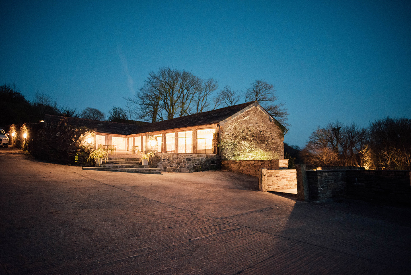 The outside of the Cowyard Barn rustic party and reception space for weddings at Pengenna Manor Cornwall wedding venue.jpg