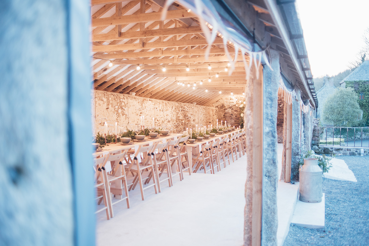 The inside of the Cowyard Barn rustic party and reception space set for an evening dinner at Pengenna Manor Cornwall wedding venue01.jpg