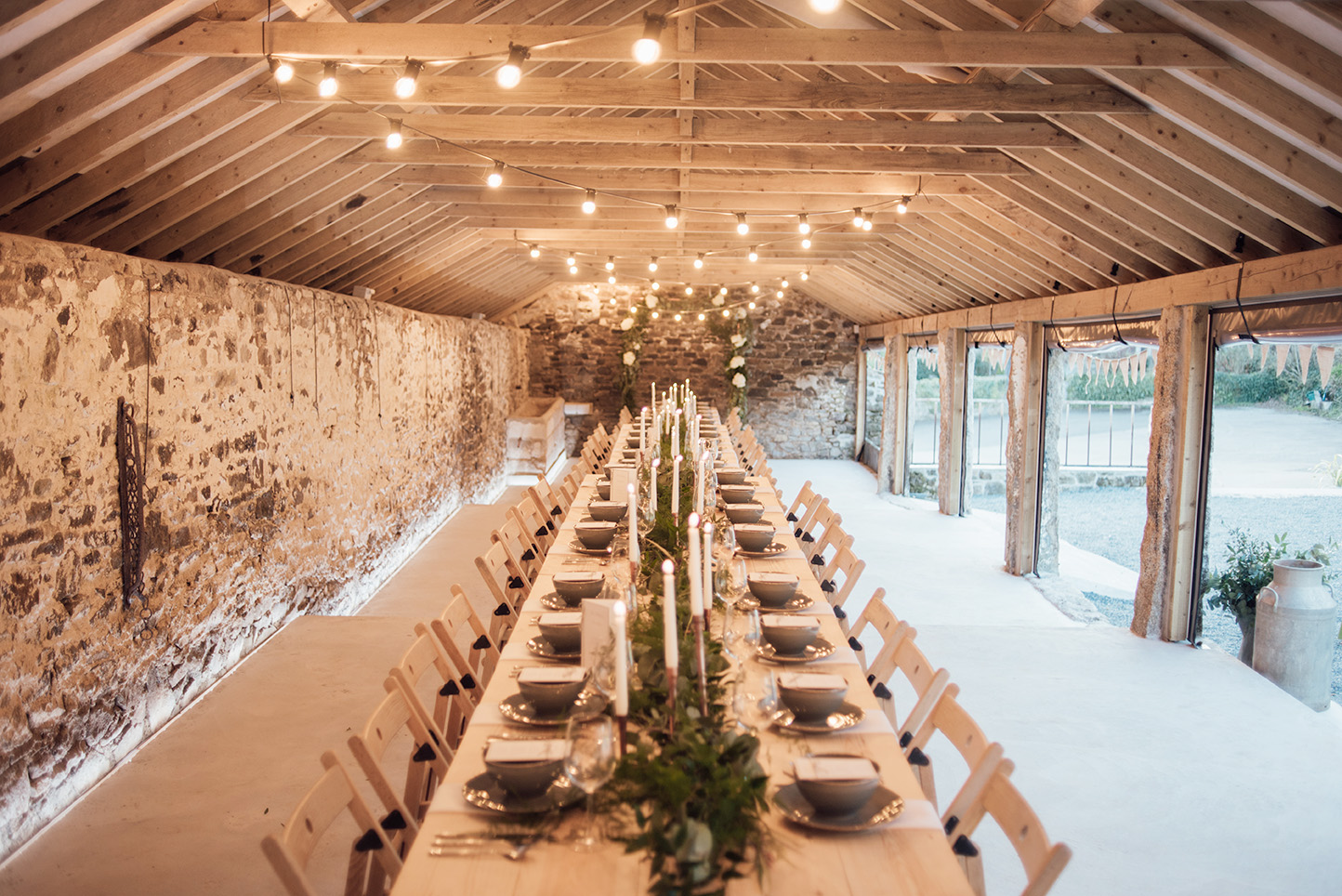 The inside of the Cowyard Barn rustic party and reception space set for a night time dinner at Pengenna Manor Cornwall wedding venue03.jpg