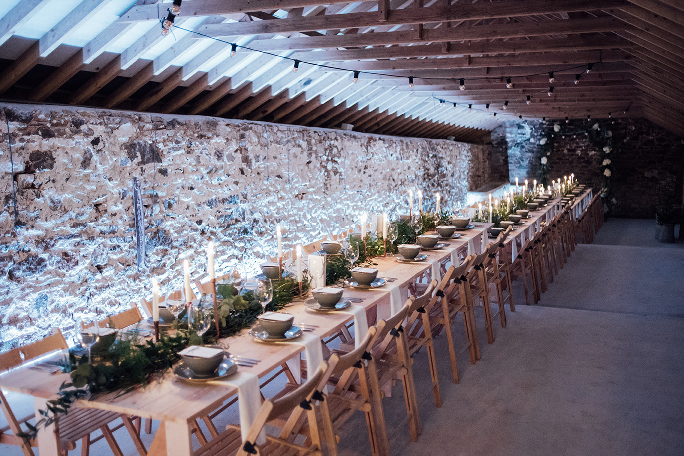 The inside of the Cowyard Barn rustic party and reception space set for a night time dinner at Pengenna Manor Cornwall wedding venue.jpg