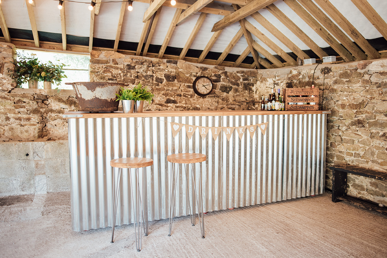The fully stocked rustic bar of the Cowyard Barn rustic party and reception space for weddings at Pengenna Manor Cornwall wedding venue04.jpg