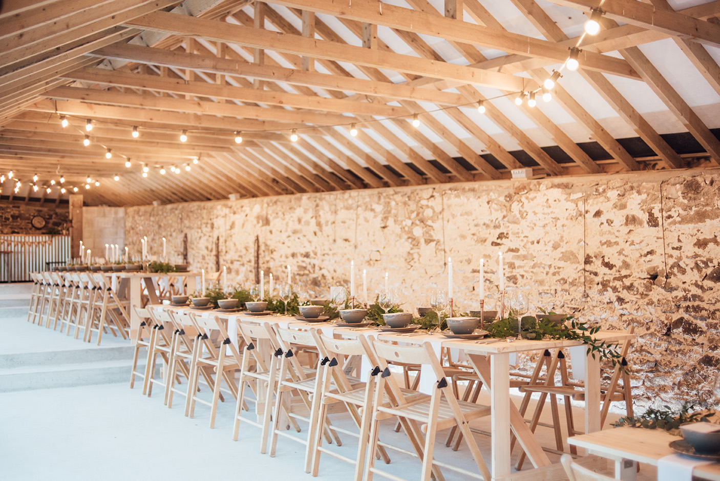 The inside of the Cowyard Barn rustic party and reception space set for an evening dinner at Pengenna Manor Cornwall wedding venue02.jpg
