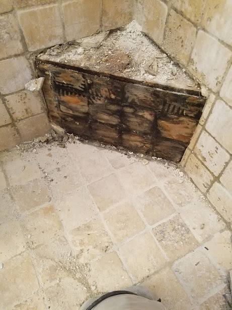 This corner bench was a wood box built on top of the shower pan with tile set directly to wood. This shower had a permanent stink to it, and it was coming from the swamp that was inside and all around this corner bench.