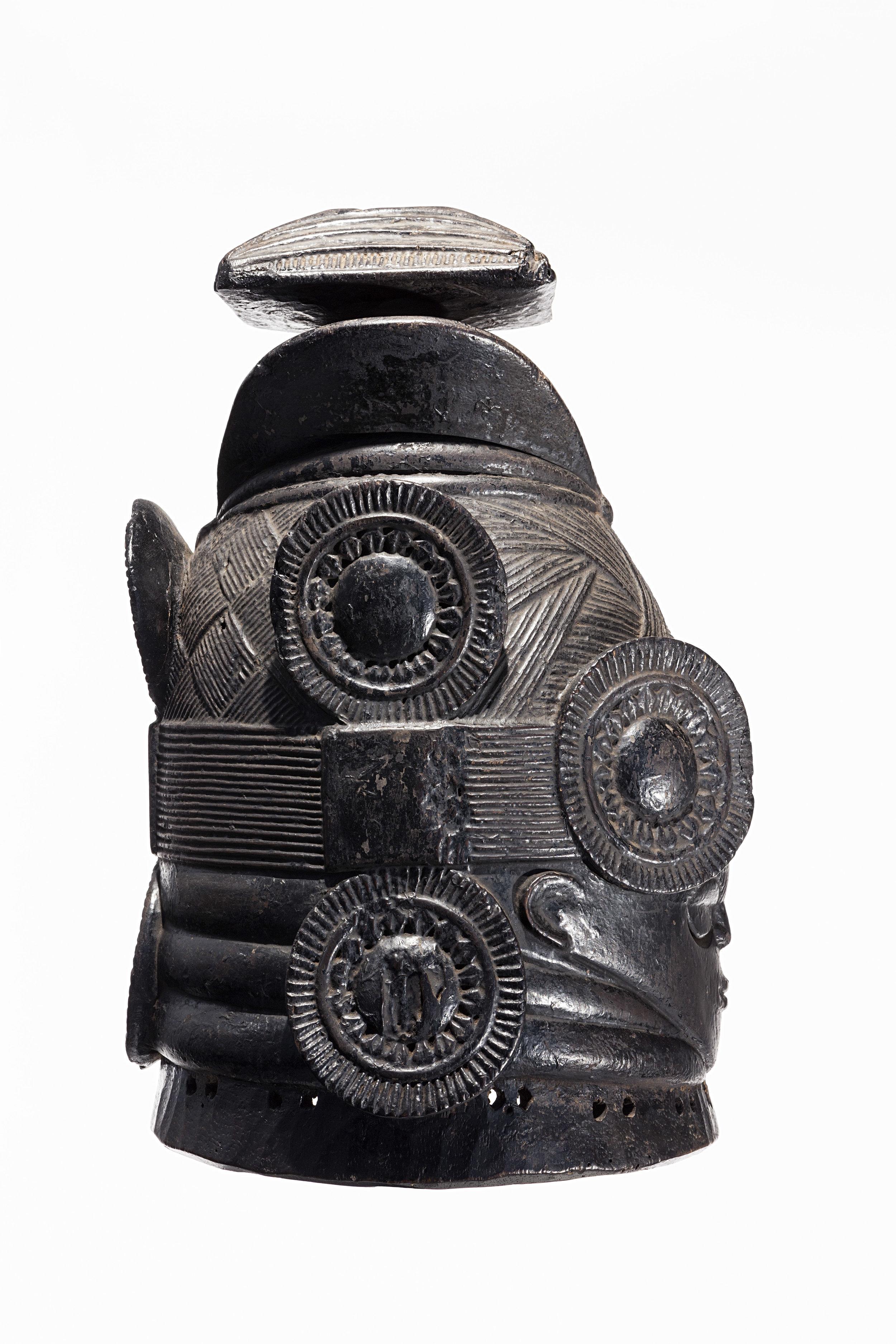 MENDE, SIERRA LEONE,  casco máscara de la sociedad femenina Sande, obra del Maestro de Nguabu. principios del siglo XX. Madera, pigmento, moneda de tres centavos  del África Occidental Británica de 1943, 39,4 x 24 x 26.