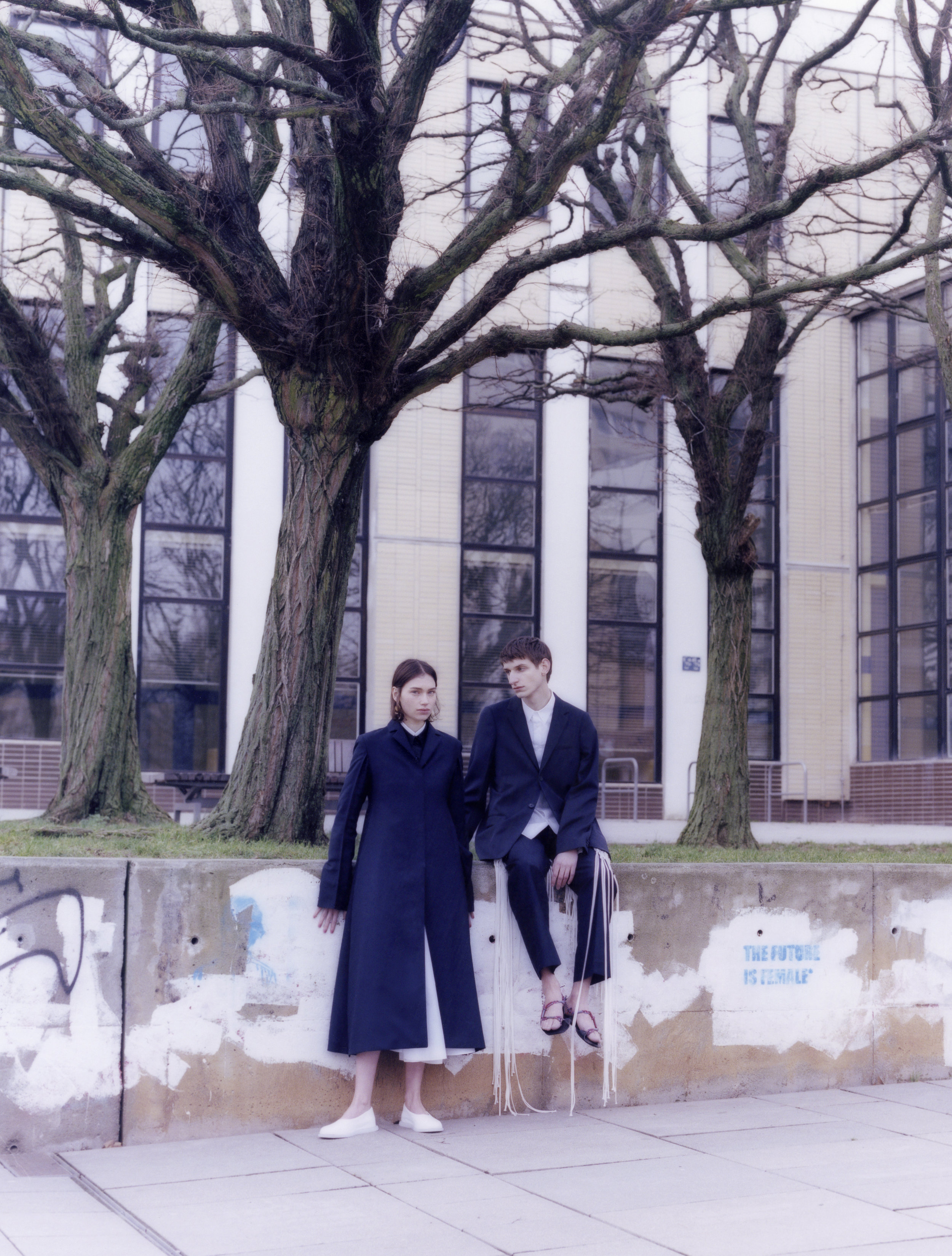 Rebecca viste chaqueta de  LEMAIRE , vestidoy abrigo de  JIL SANDER  y zapatos de  CAMPER.  Adrian viste  total look  de  JIL SANDER .