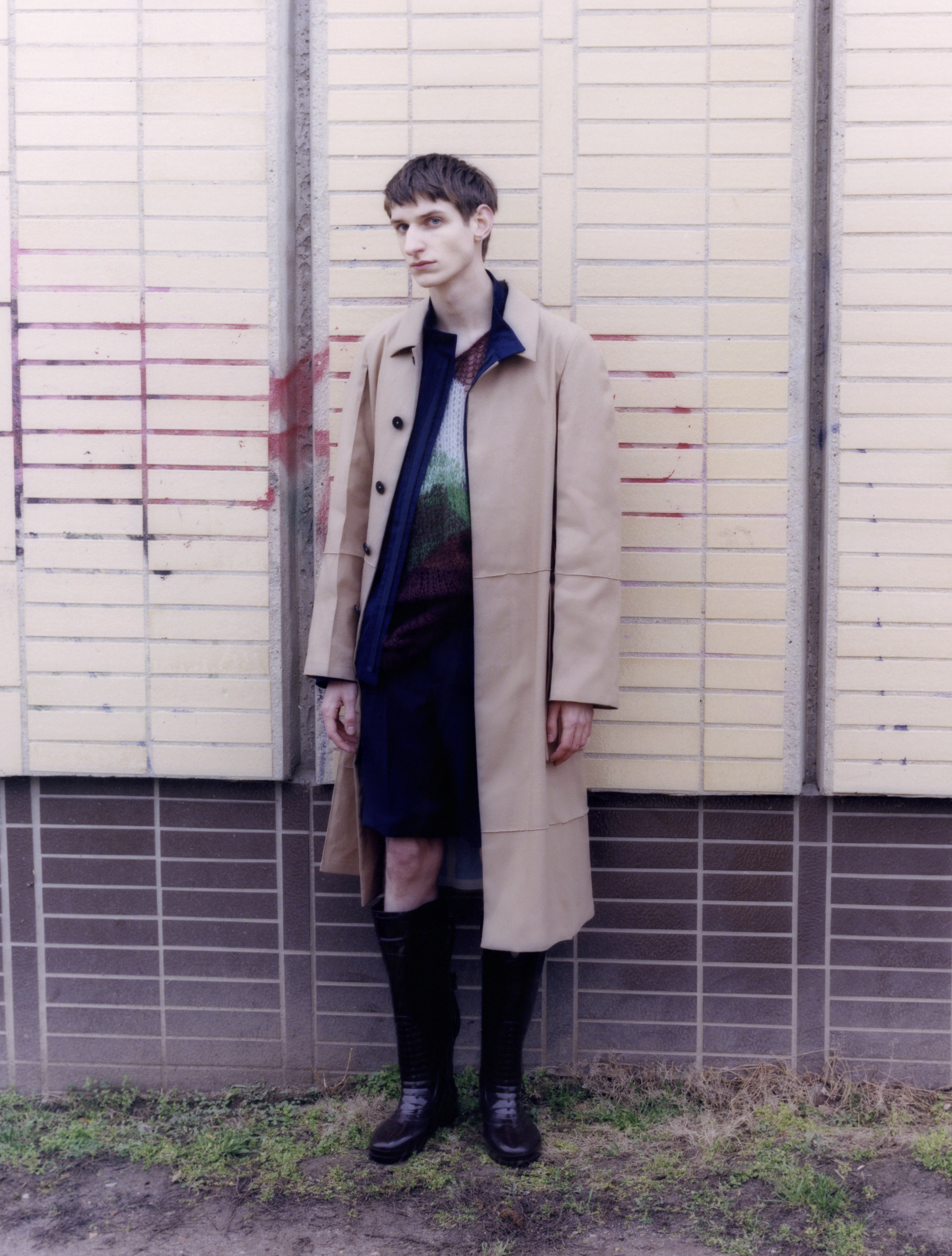 Adrian viste abrigo, camiseta y pantalón, todo de  JIL SANDER . Chaqueta de  LEMAIRE  y botas de  RAF SIMONS .