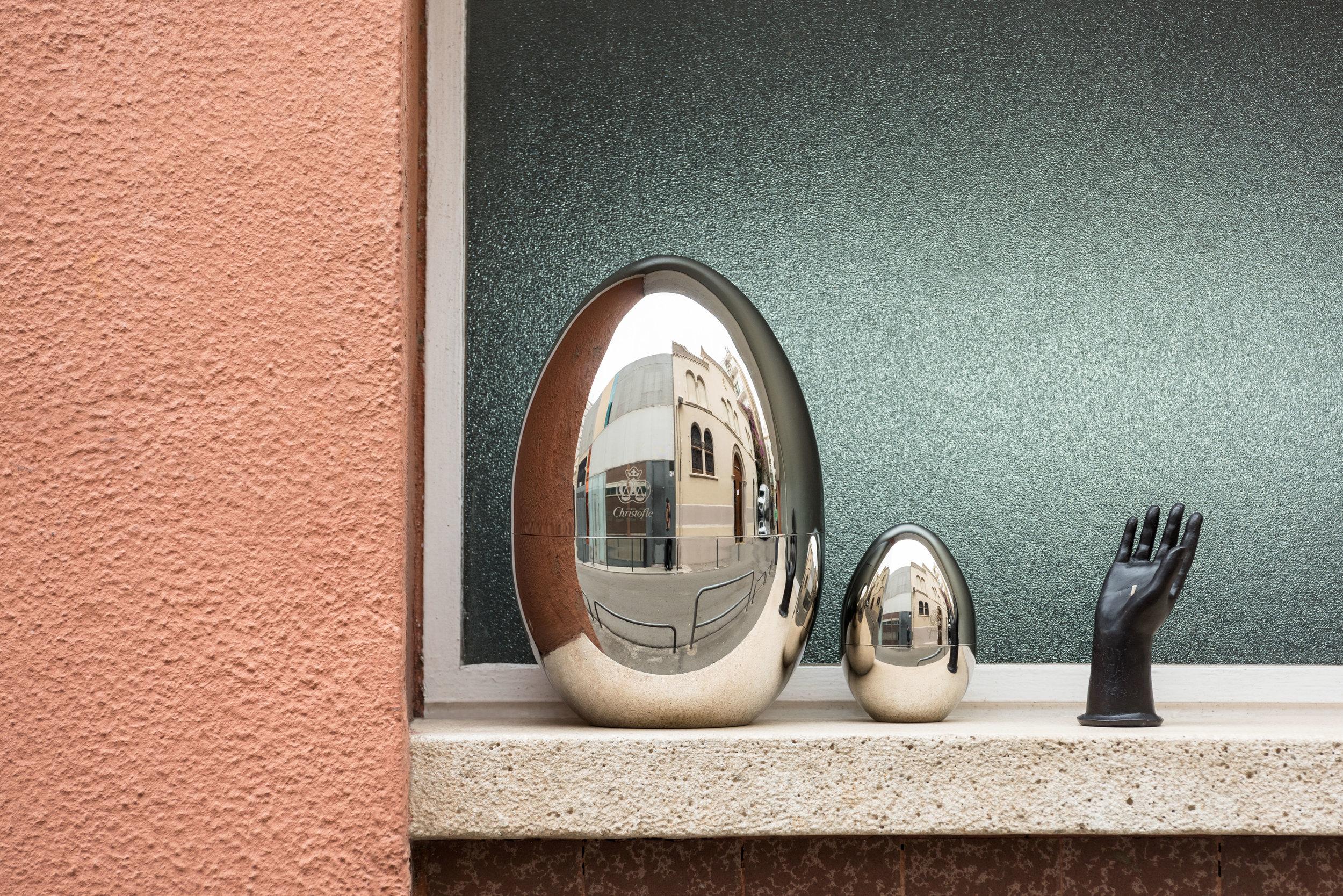 Soporte de cubertería en forma de huevo de  CHRISTOFLE  y vela en forma de mano de  CIRE   TRUDON .