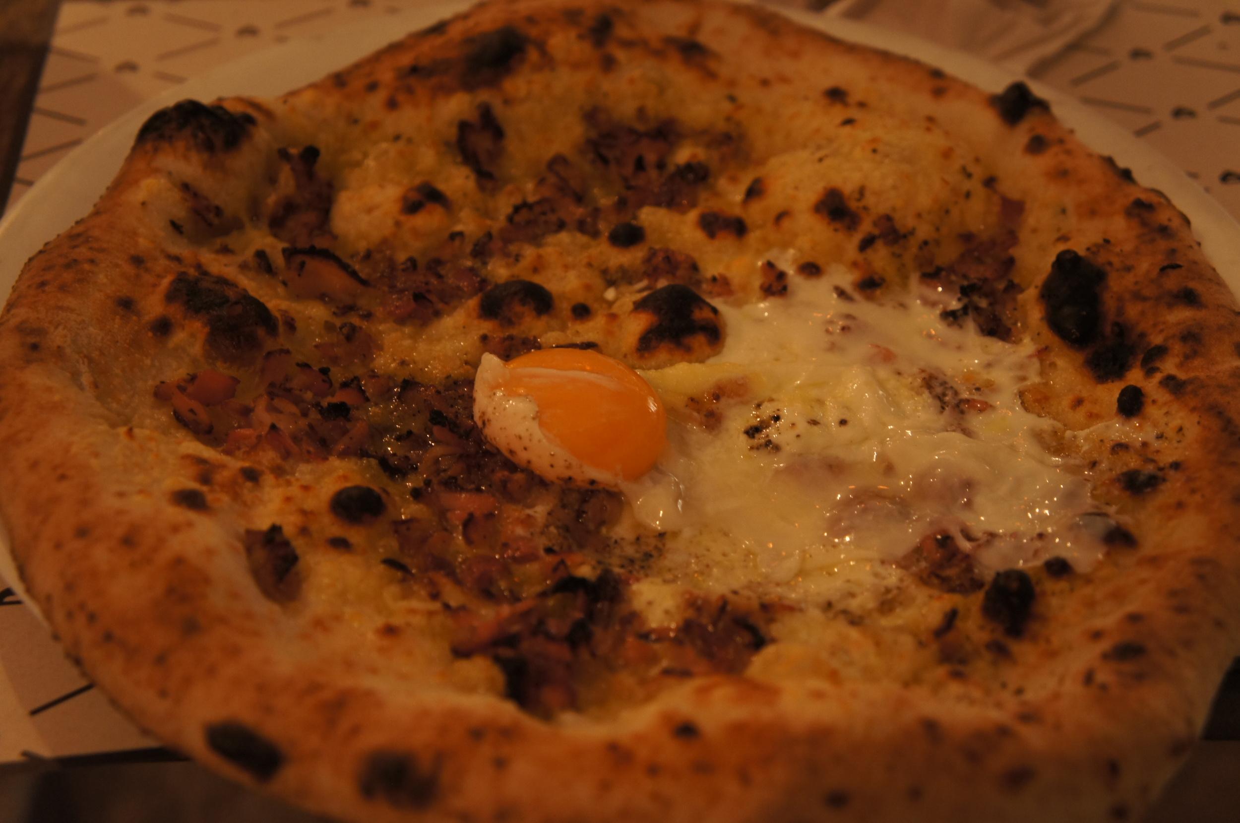 Um dos pratos foi a pizza Carbonara. Ela é um sabor super fotogênico, não é? Essa versão leva pancetta e pimenta-do-reino, que dá um toque diferente. As pizzas são em tamanho individual.