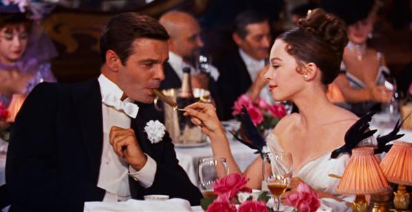 Actress Leslie Caron lights a cigar in the movie Gigi.