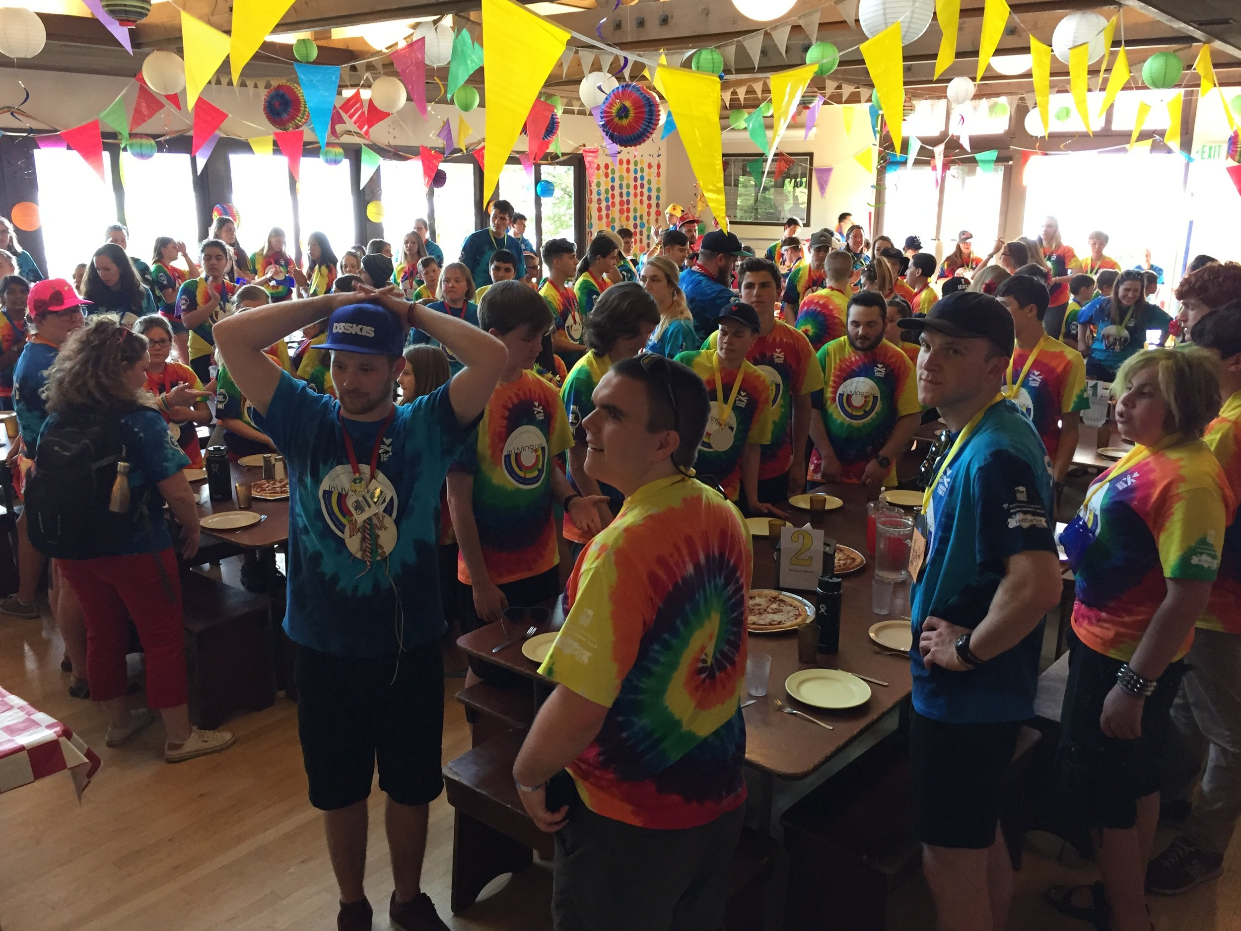 Campers and staff stand to sing a camp grace