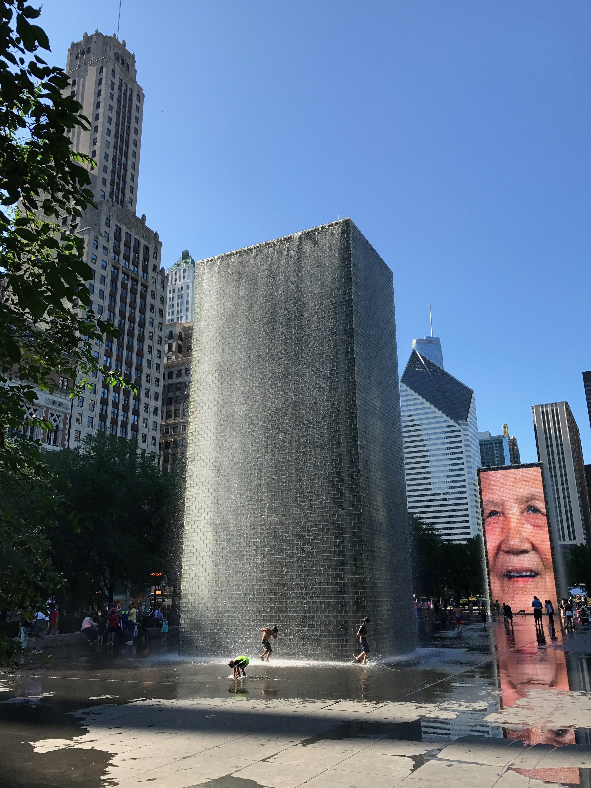 Designed by Designed by Spanish artist  Jaume Plensa , the  Crown Fountain in  Millennium Park  is a major addition to the city's world-renowned public art collection.  The fountain consists of two 50-foot glass block towers at each end of a shallow reflecting pool. The towers project video images from a broad social spectrum of Chicago citizens, a reference to the traditional use of gargoyles in fountains, where faces of mythological beings were sculpted with open mouths to allow water, a symbol of life, to flow out.  Plensa adapted this practice by having faces of Chicago citizens projected on LED screens and having water flow through an outlet in the screen to give the illusion of water spouting from their mouths. The collection of faces, Plensa's tribute to Chicagoans, was taken from a cross-section of 1,000 residents.  The fountain's water features operate during the year between mid-spring and mid-fall, while the images remain on view year-round.