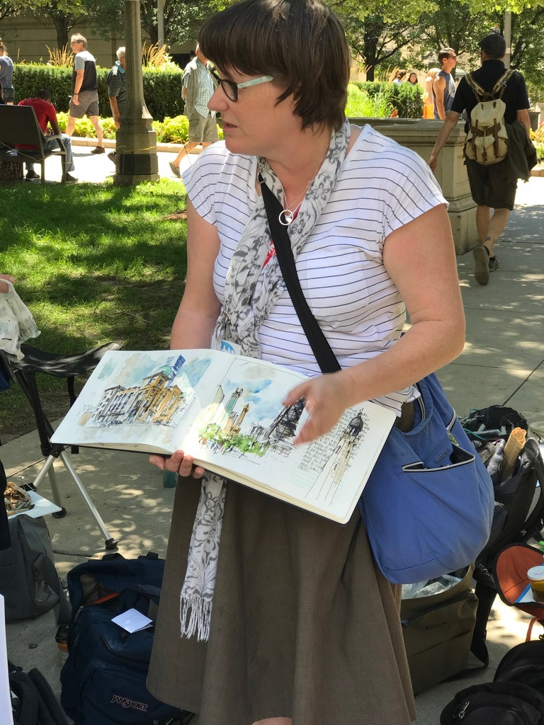 Liz explaining concepts and showing examples from her sketchbook