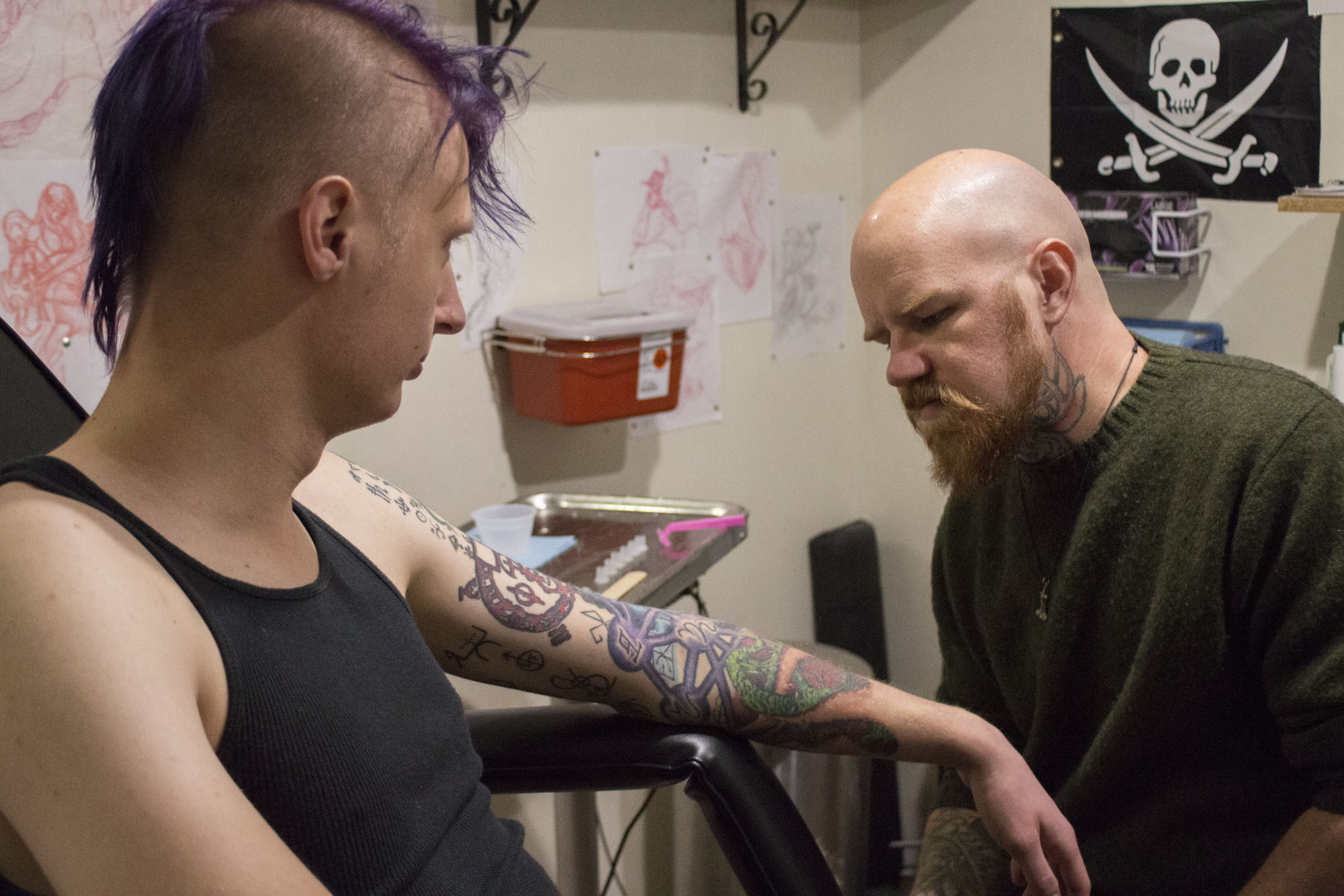 """Bruce examines his progress on Paterson's tattoo sleeve before deciding where he wants to pick up tattooing. Bruce has been working on tattooing Paterson's sleeve for almost two years. """"He won't let me tell him my other tattoo plans until we finish this,"""" Paterson said half-grudgingly."""