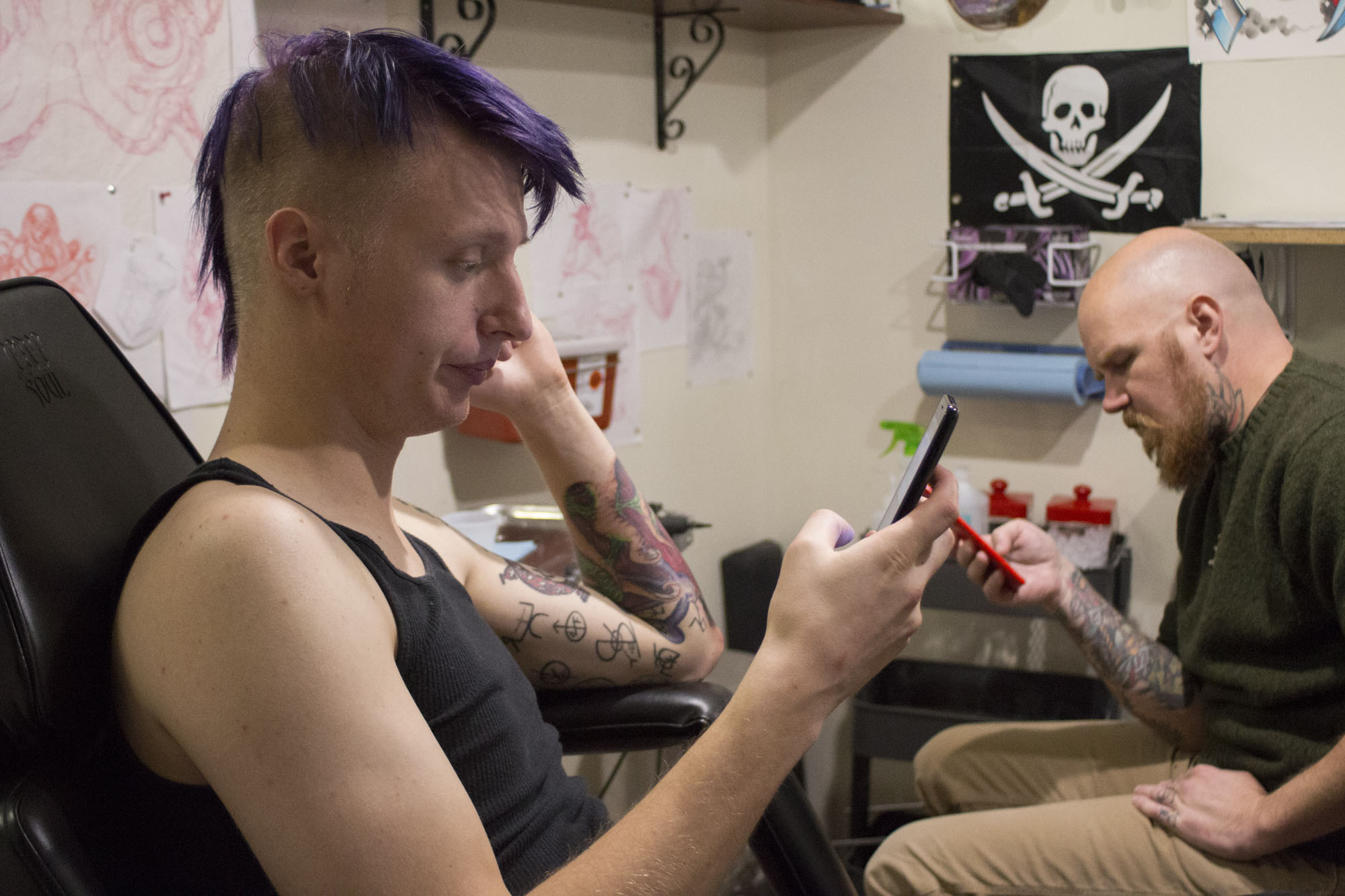 Paterson and Bruce take a break from tattooing Paterson's elbow. Paterson and Bruce both immediately grabbed their phones after almost an hour and a half of work on Paterson's sleeve.