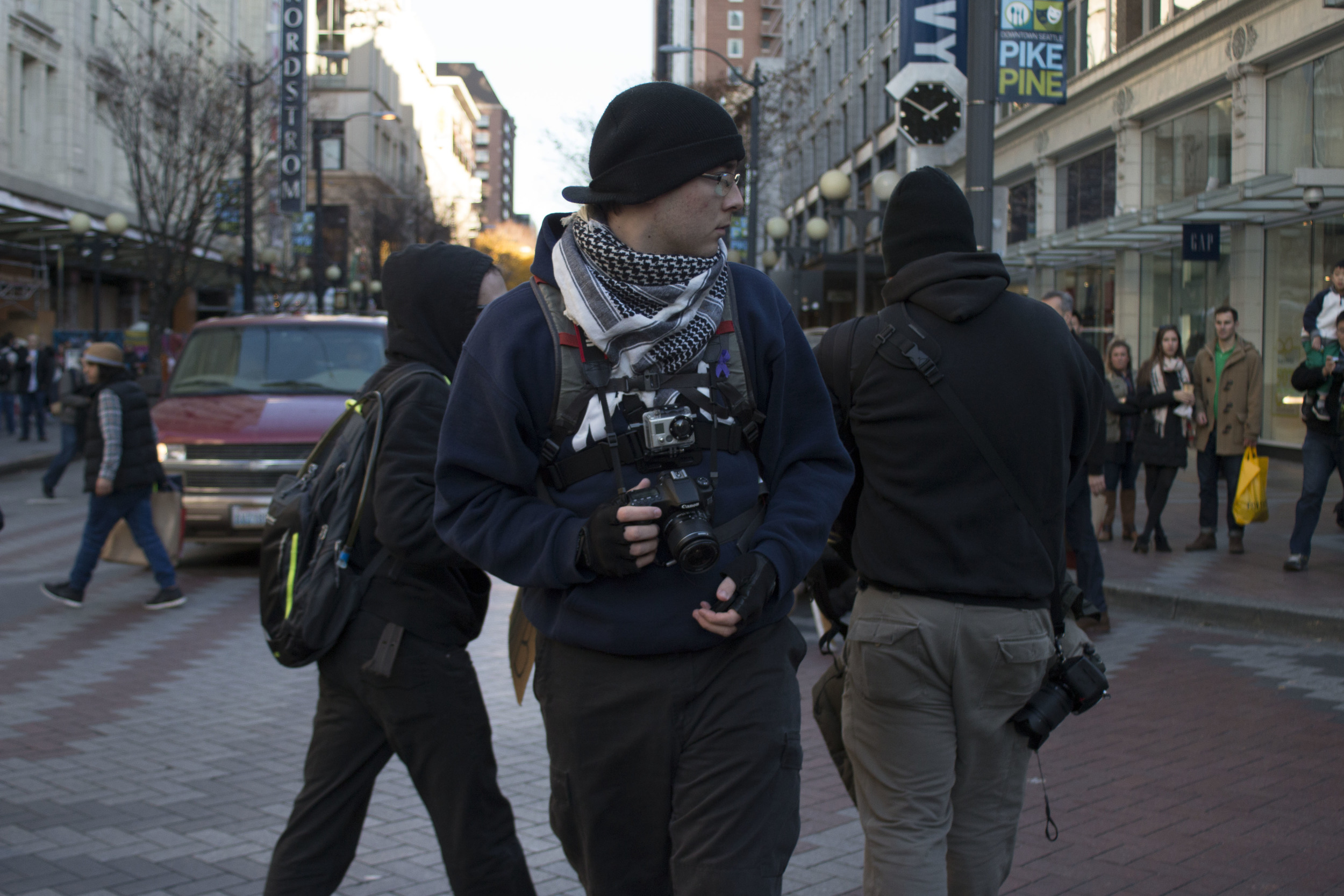 Nelson glances around while photographing the Black Friday Black Lives Matter protest as the crowd moves through the streets of downtown Seattle. Nelson said he always tries to be aware and keep an eye on his surroundings.
