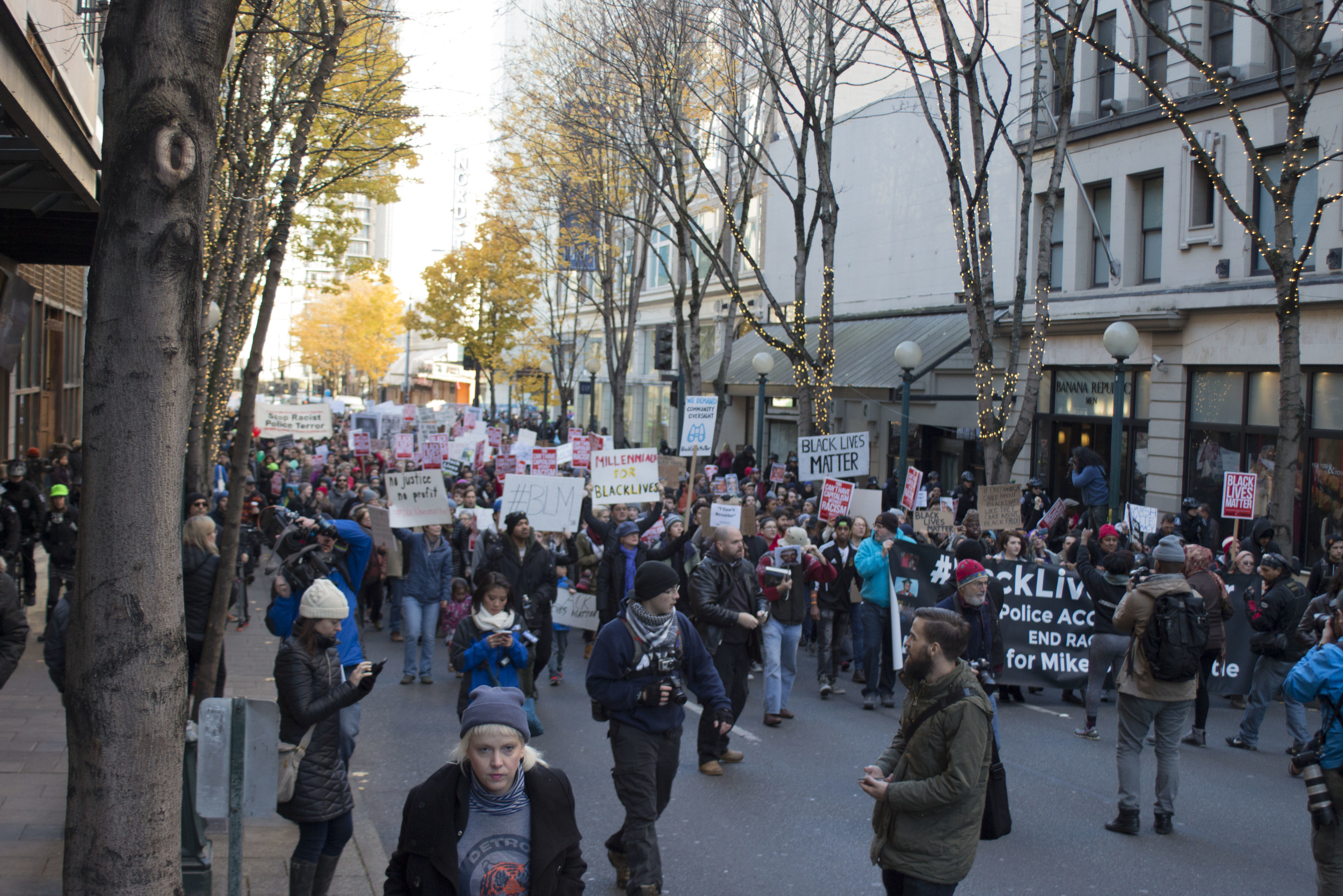Nelson walks toward the front of a crowd of protesters while photographing the Black Friday Black Lives Matter protest as the crowd moves through the streets of downtown Seattle.