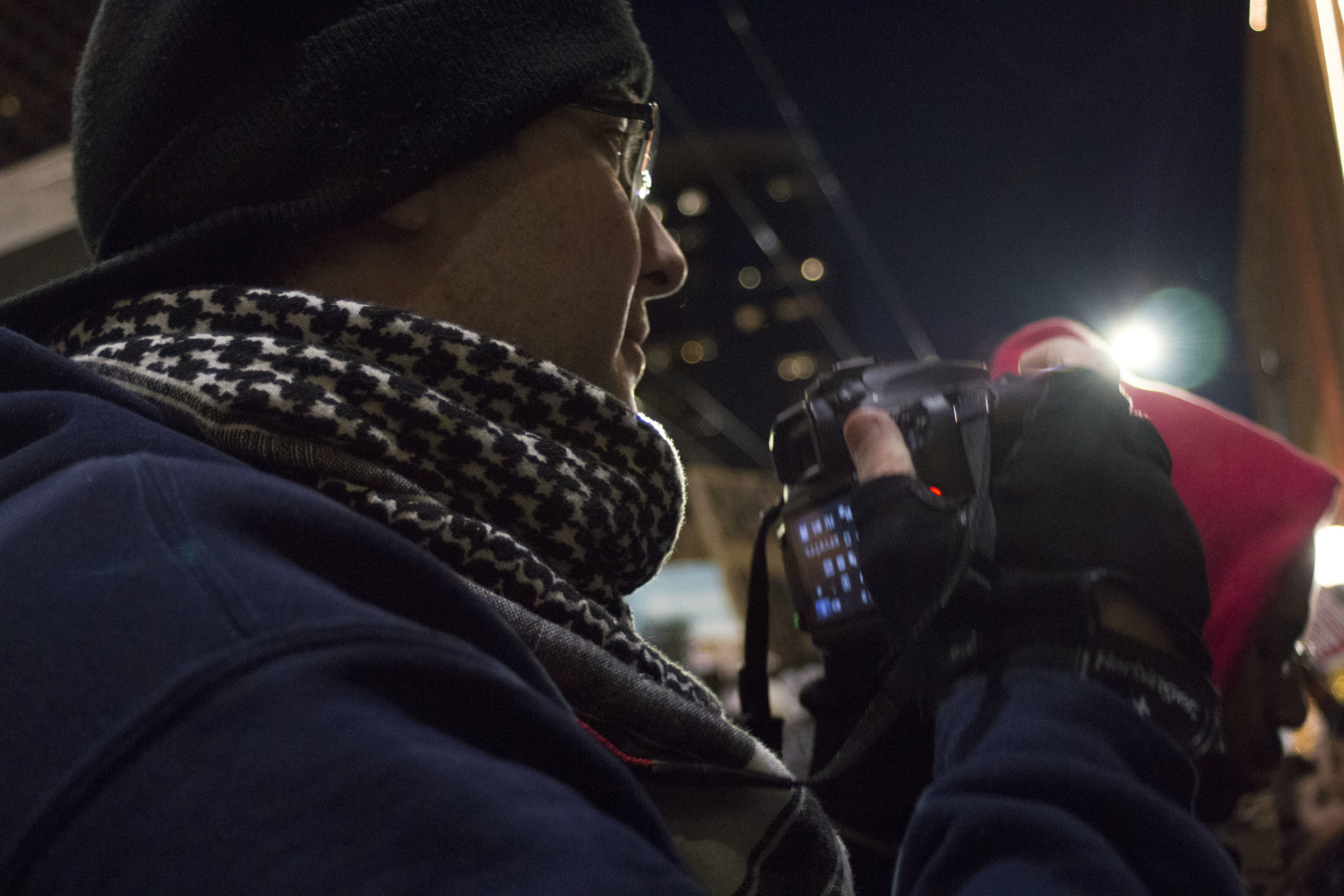 Toward the end of the Black Friday Black Lives Matter protest, Nelson peaks over his camera and watches performers and protesters vie for attention during the annual tree lighting ceremony at Westlake Center.