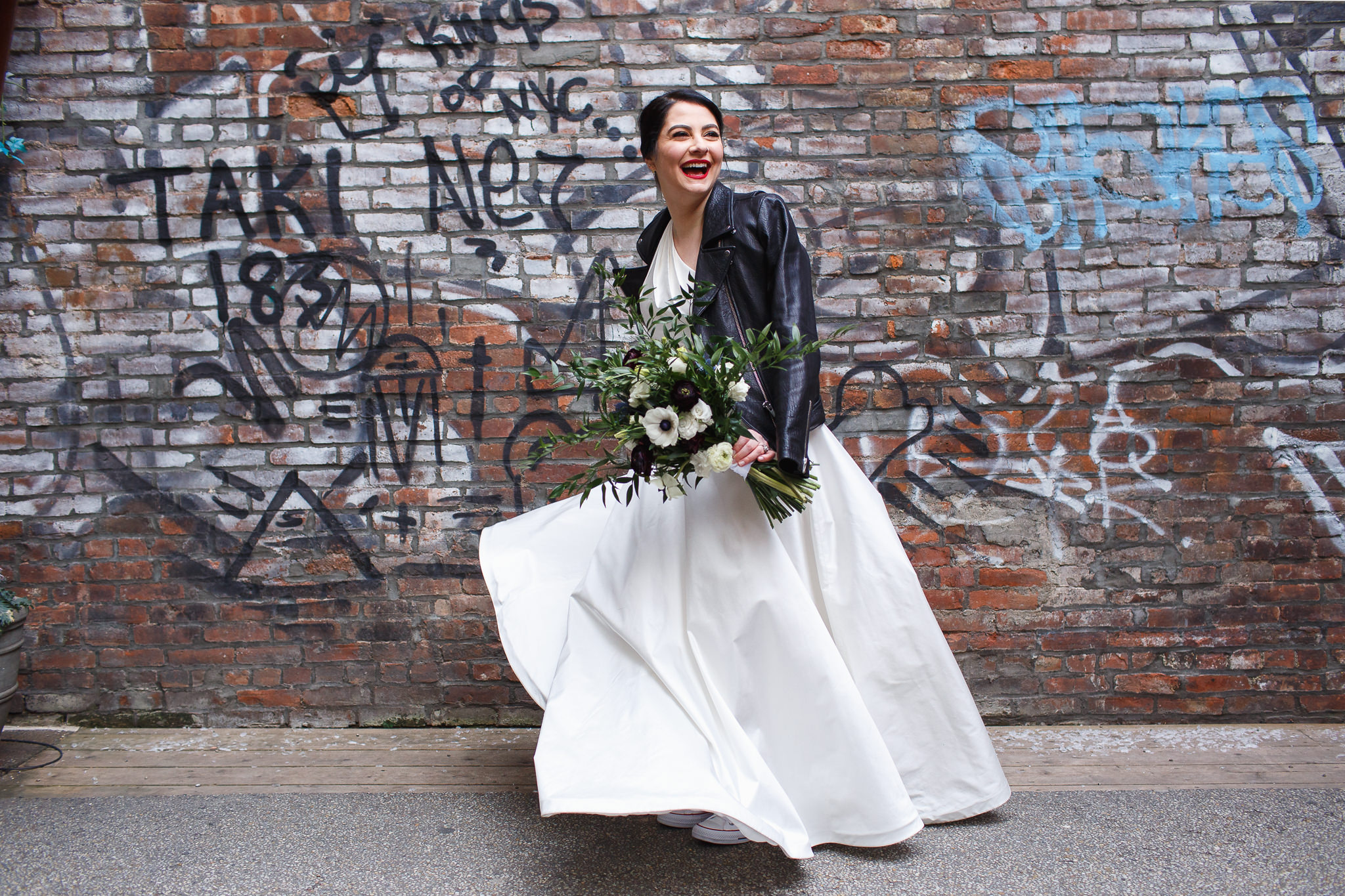 Bride in a white dress and black leather jacket spins in front of a graffiti wall with her Stems Brooklyn bouquet