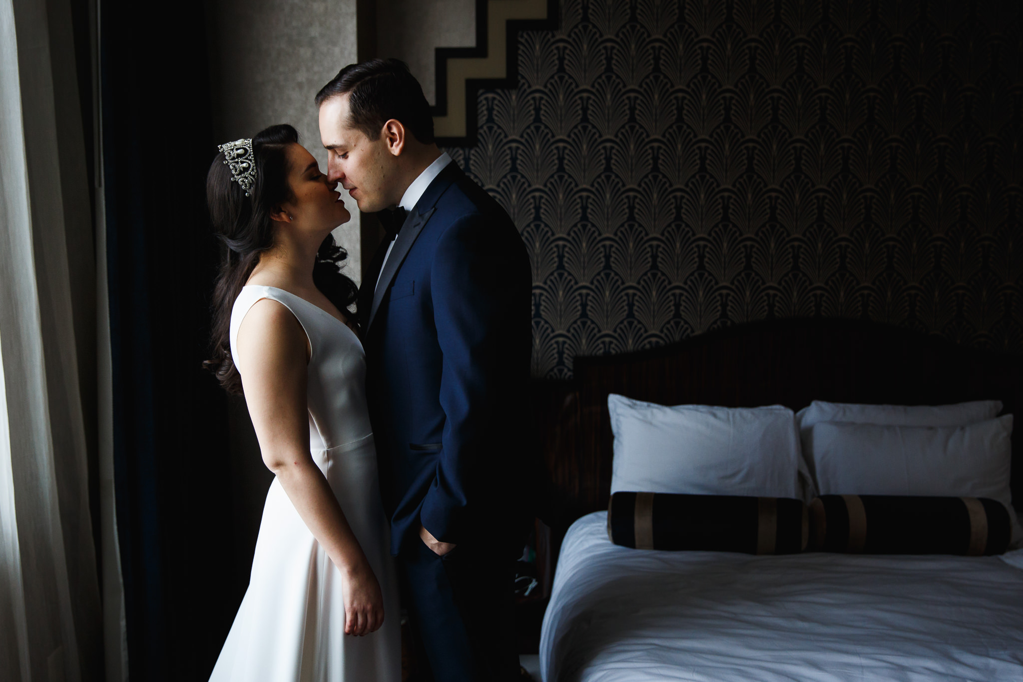 Couple getting ready together before wedding. Kissing after putting on wedding attire. Royal wedding inspiration. Wedding tiara and blue suit.
