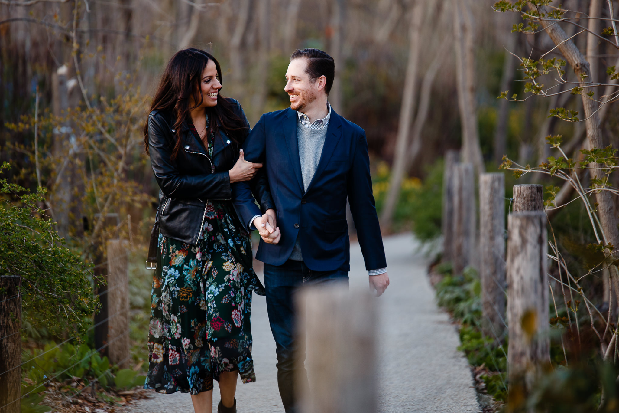 Couple walks hand in hand down path in brooklyn bridge park during their engagement session