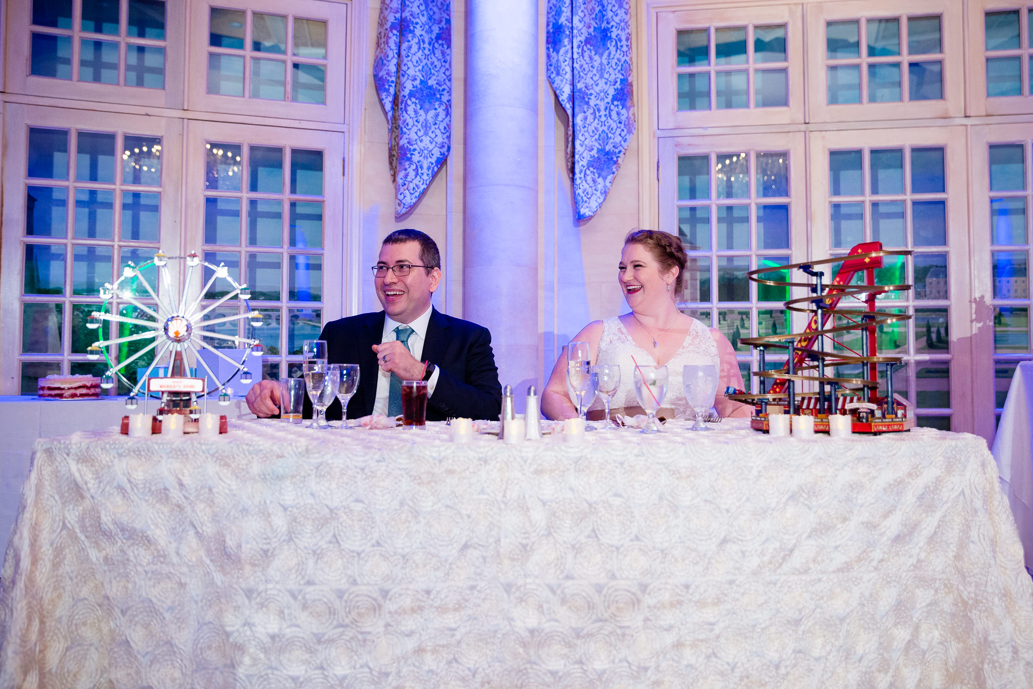 couple laughs at wedding party speeches