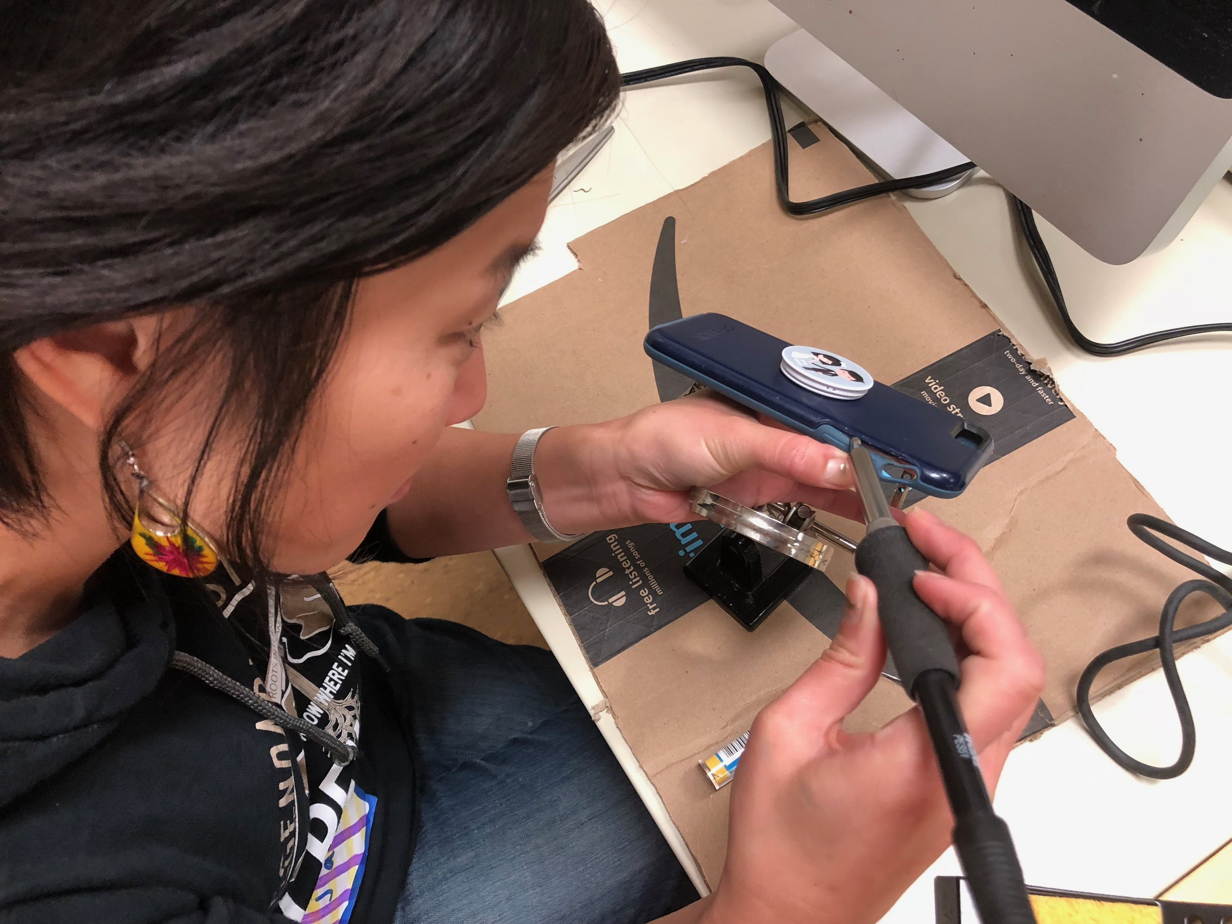 Agency  by  Design Oakland fellow Jane Lee uses a soldering iron to repair her phone.