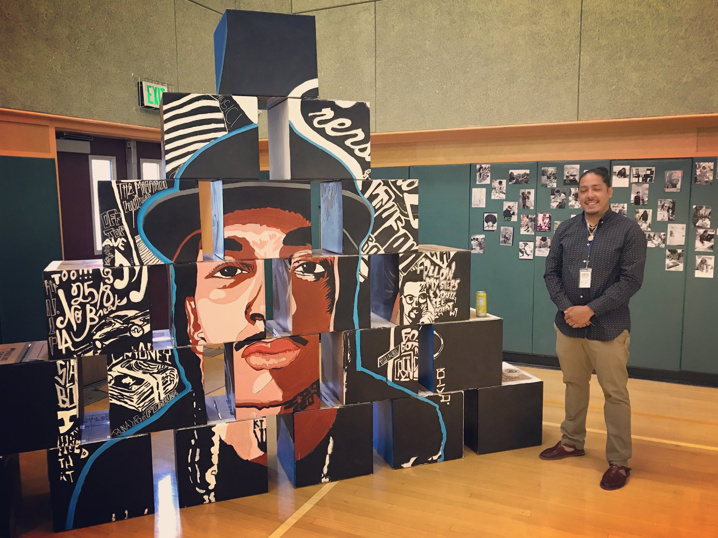 Kurt standing by his students' collaborative mural of Nipsey Hussle.