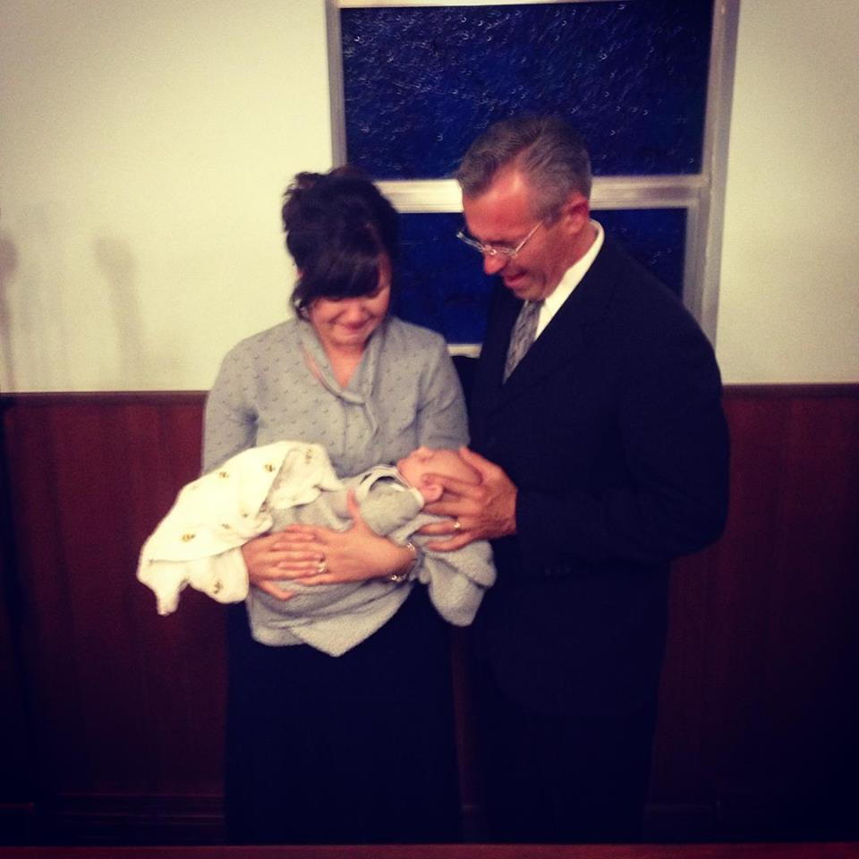 Melissa's father praying over her and Asher.