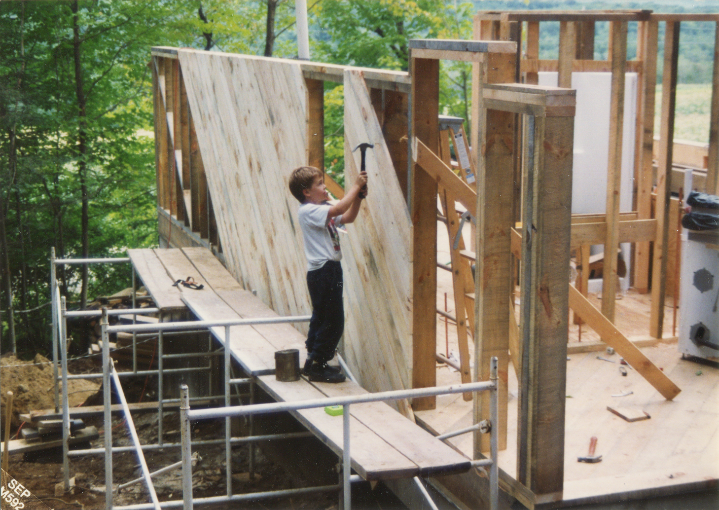 Ben, age 8, hammers pine sheathing onto the north wall of his family's Monroe home.