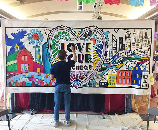 "It's so awesome to see projects come together. I designed and painted the outlines of this banner for young people to engage with- with paint and written reflections of their thoughts on ""neighbor"". I'm happy to see that people felt free and uninhibited by traditional notions of what color things ""should"" be."