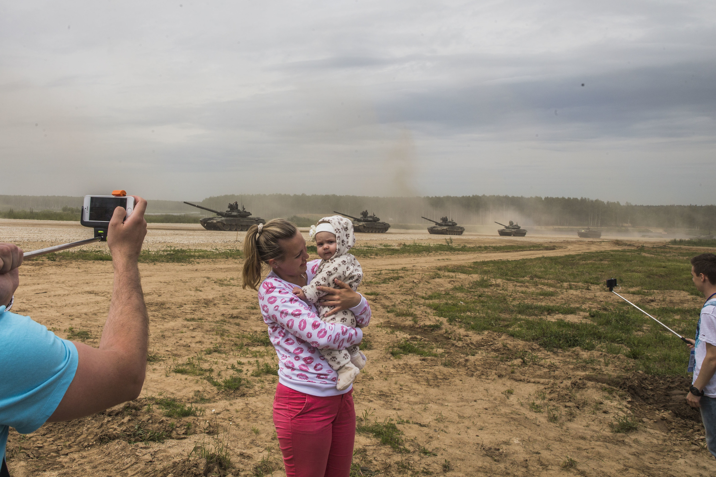 Visitors pose for pictures as Russian army's tanks parade at Alabino shooting range 40 kilometers from Moscow