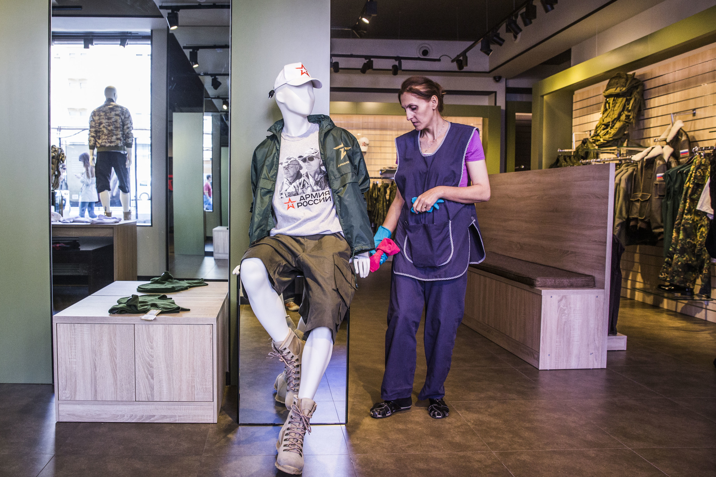 A cleaning woman wipes the mannequin dressed in a T-shirt with president Putin's face at a newly opened Russian army's merchandise shop on Moscow's central street