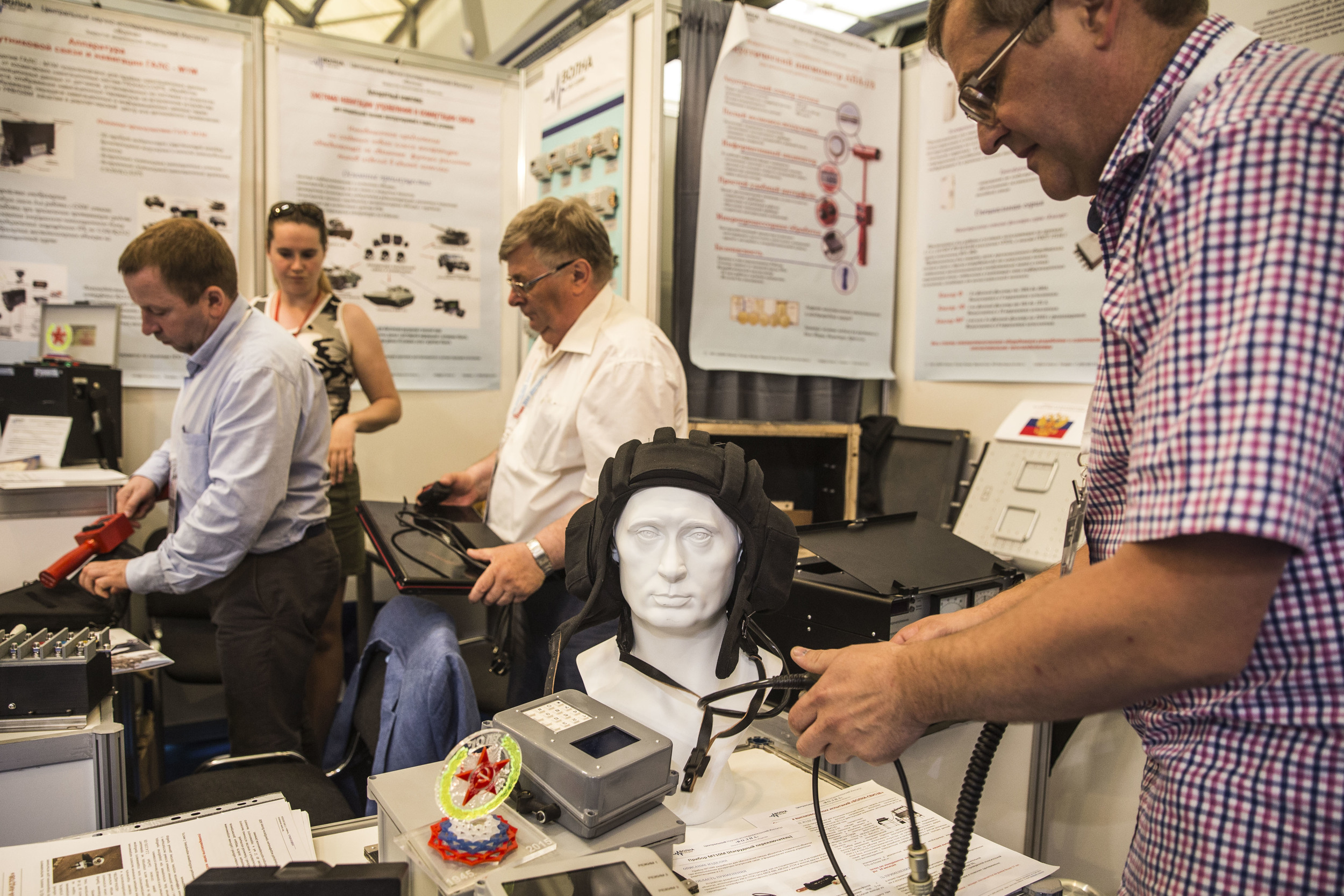 Man puts a tank driver's helmet out of a Putin-faced mannequin at a static part of a military expo in Patriot park 40 kilometers from Moscow