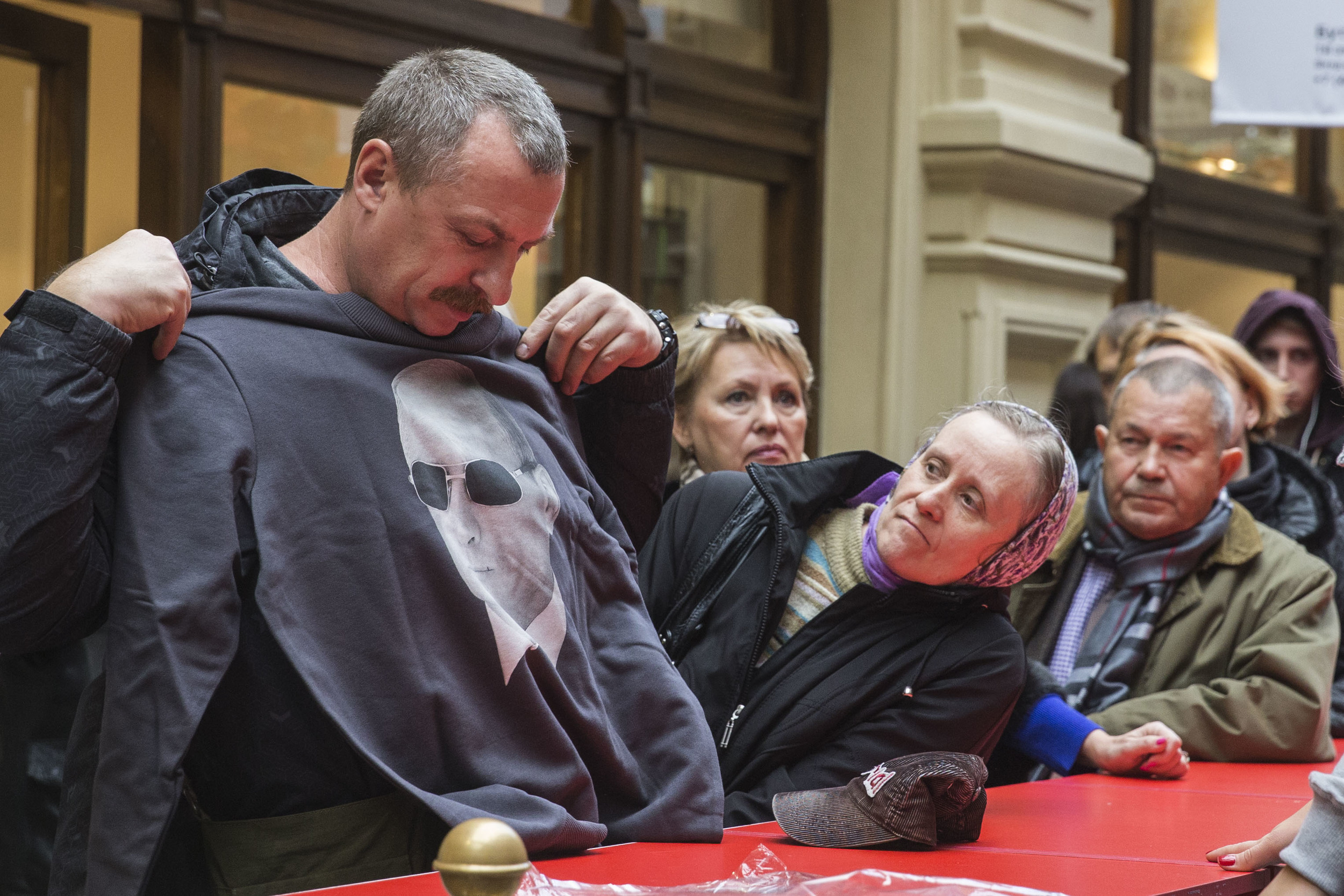 Man tries on a hoodie with president Putin's face on it following the first day of this merchandise being on sale at main department store (GUM) in Moscow