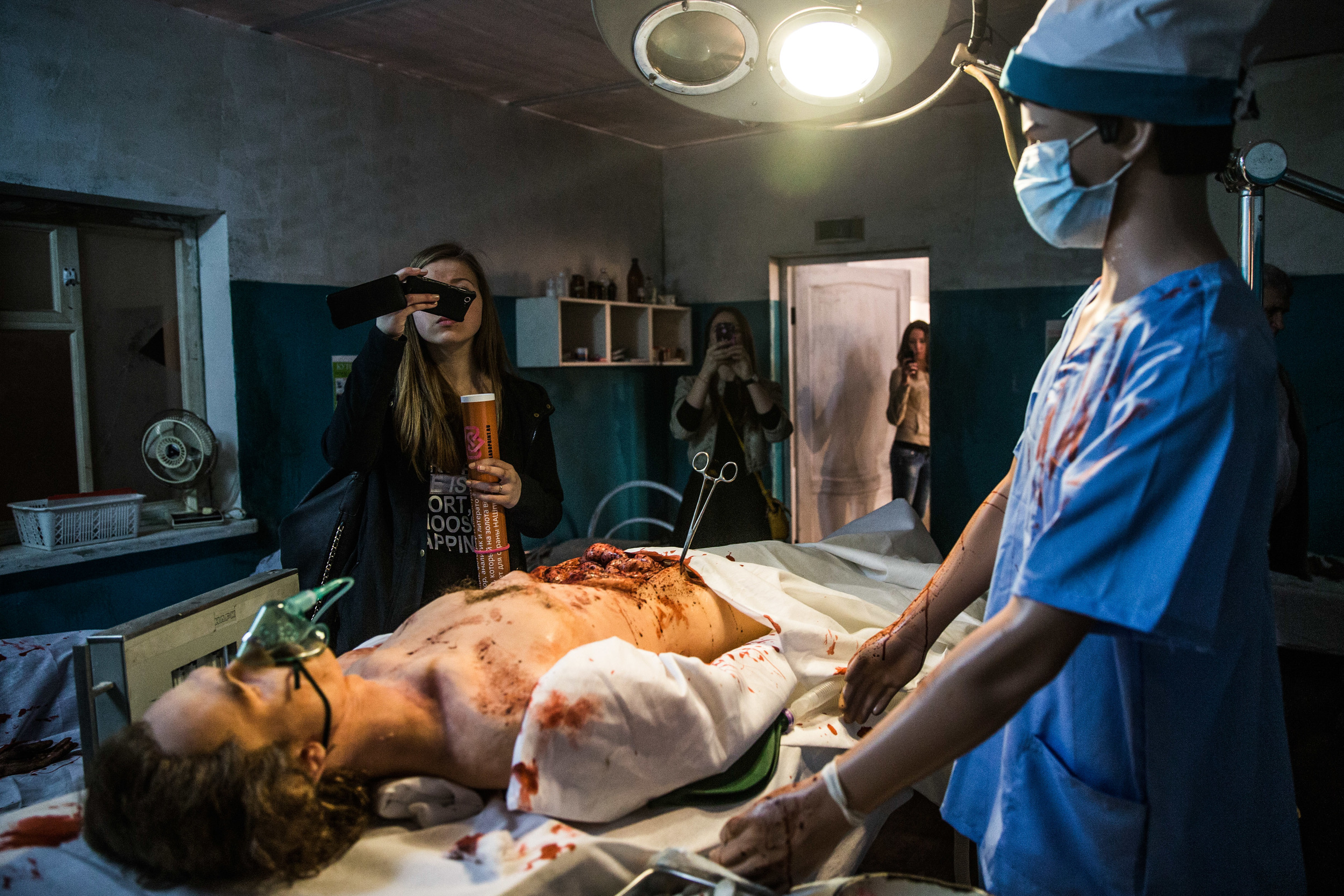 """Visitors photograph a mock up hospital room that is a part of exposition at """"Donbass. Material evidence"""" exhibit in Moscow"""