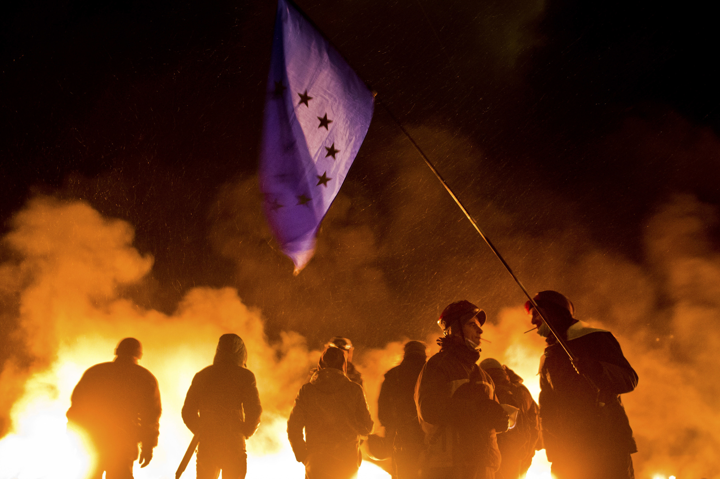 Protesters chat with each other holding EU flag during clashes with police forces in Kyiv, Ukraine.