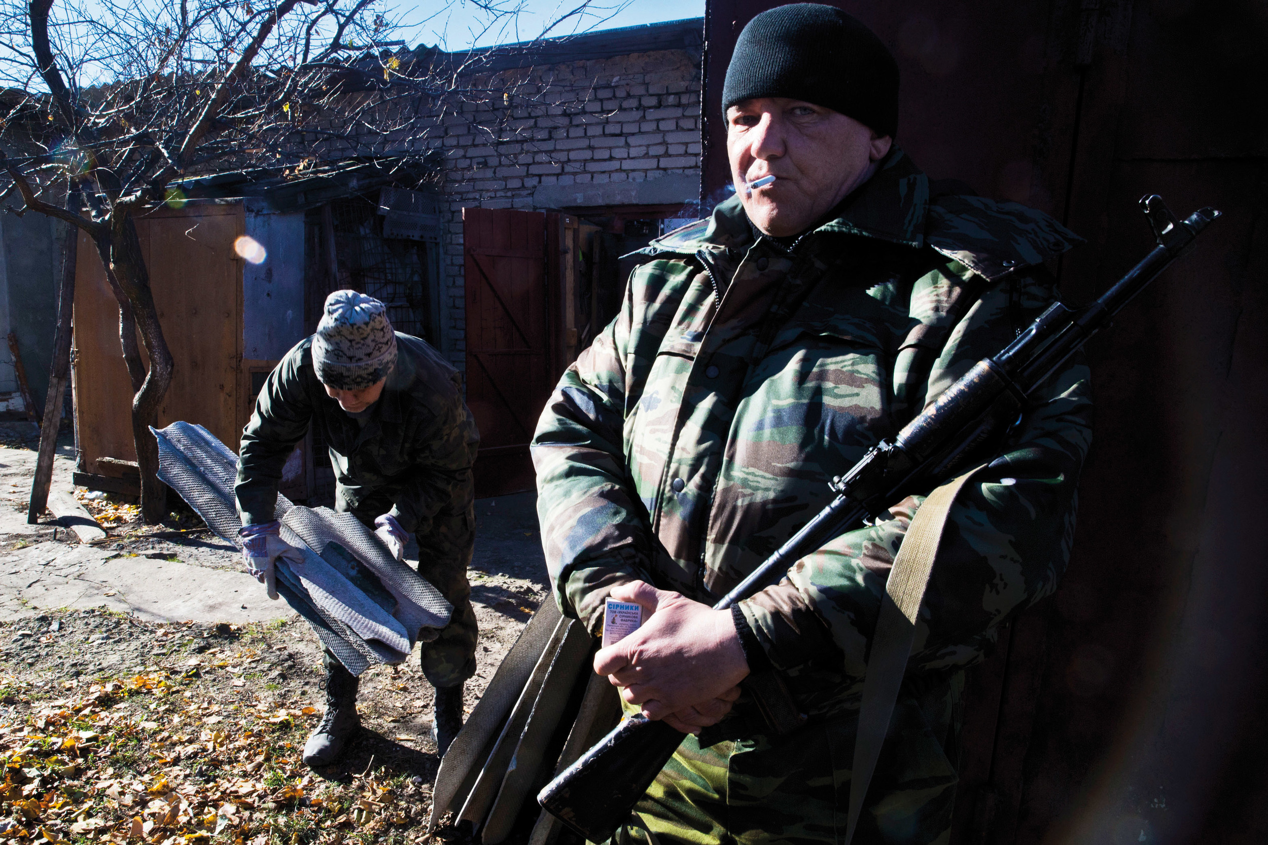 Pro-Russian fighter is seen guarding Ukrainian POWs as they are forced for labour in Ilovaysk