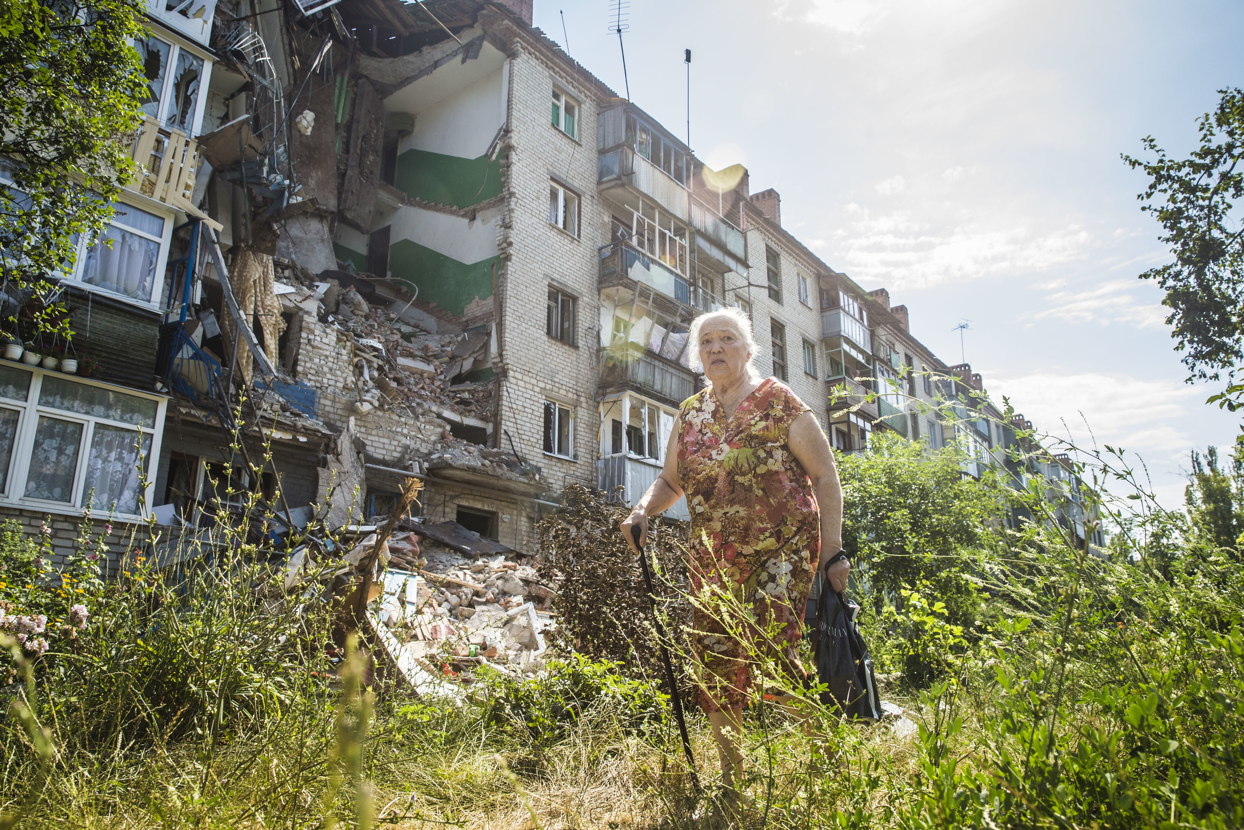 Woman passes by a destroyed building in Sloviansk