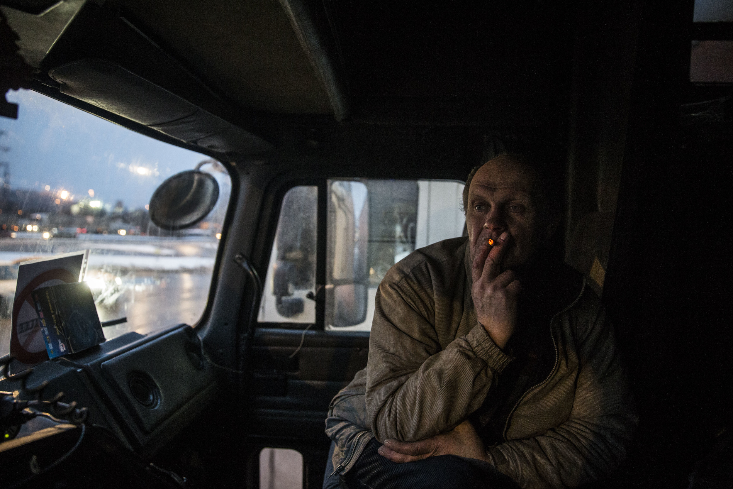 A truck driver smokes as he participates in a strike against new tax on his business. December 2015