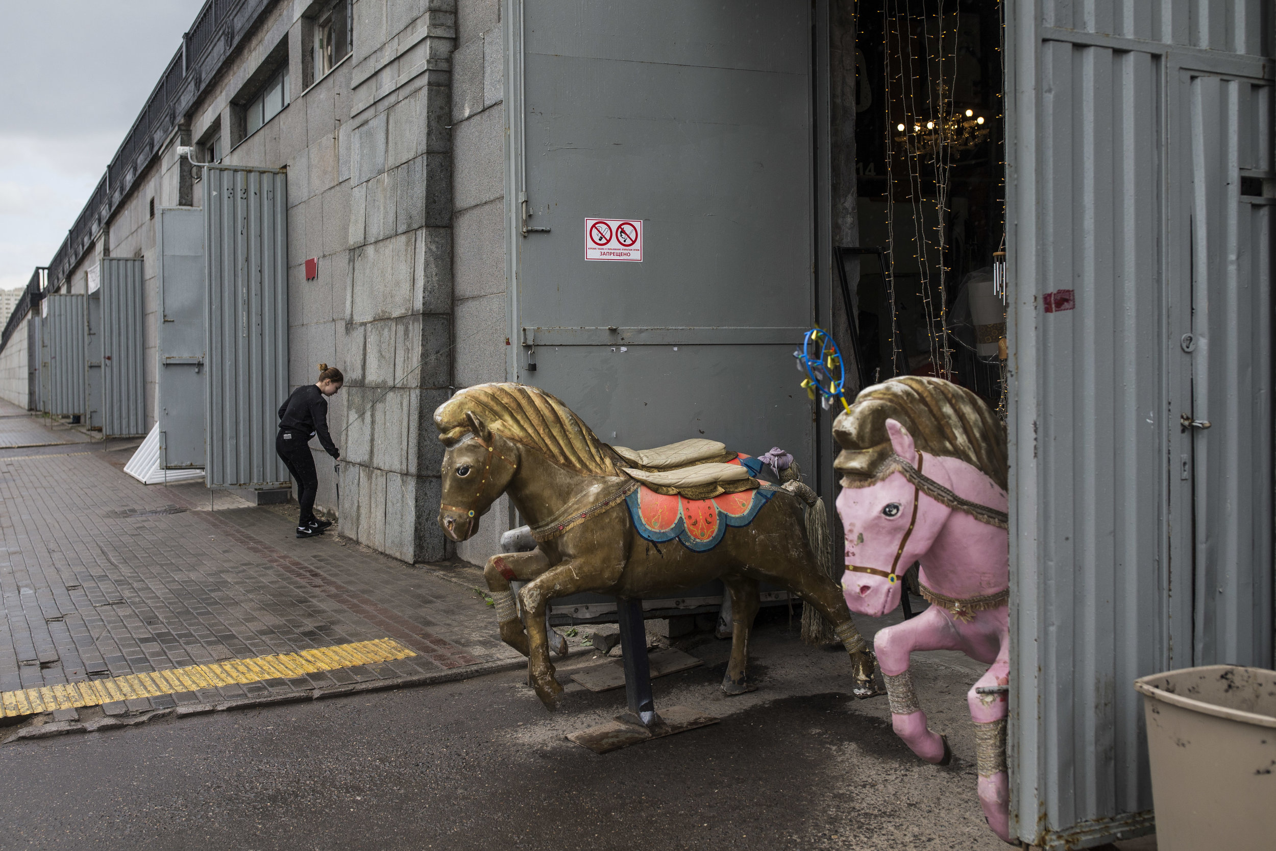 Old caroussel horse looks out of a junk store in Moscow