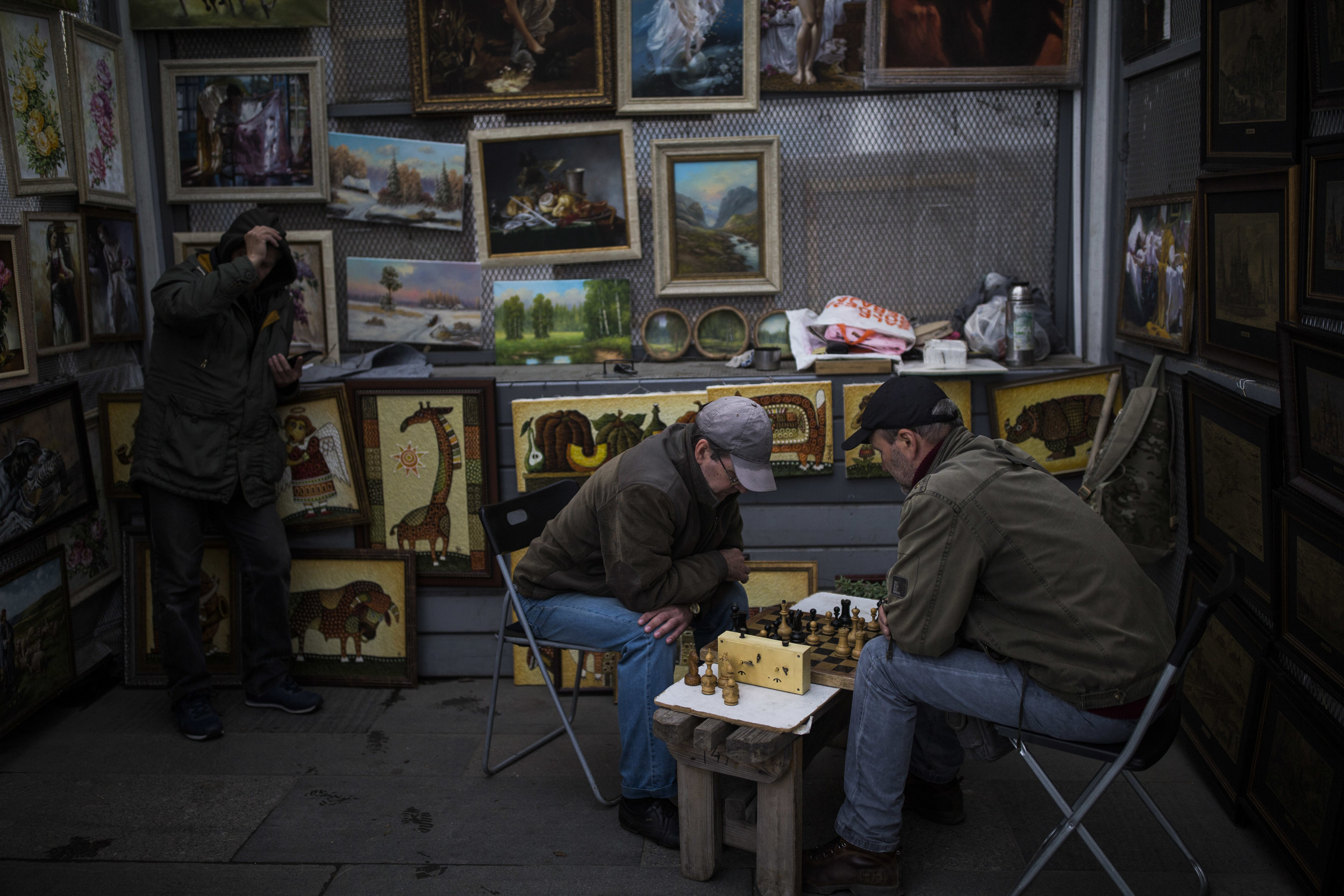Artists are playing chess as they hide from the rain at vernissage next to Tretyakov gallery in Moscow
