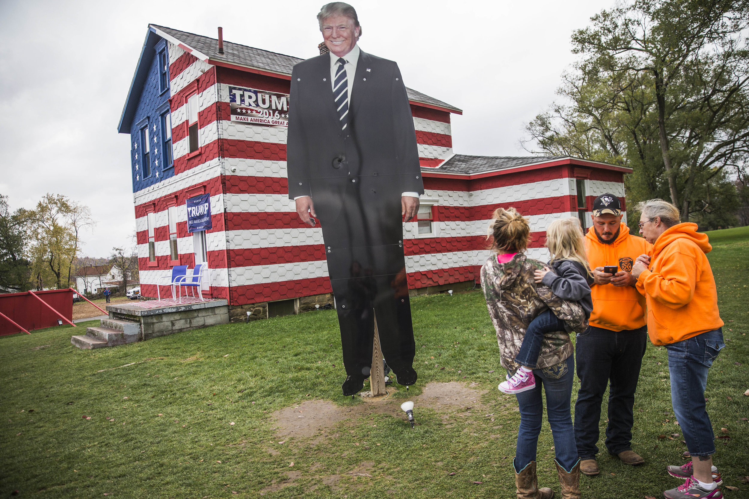 Visitors stand in front of four-meters-high Donald Trump's portrait that was erected next to the Trump House in Pennsylvania's Westmoreland county.