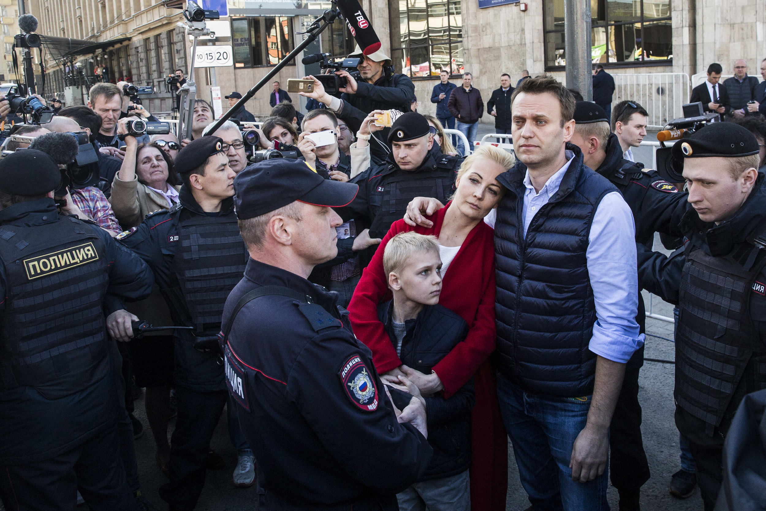 Alexey Navalny, his wife Yulia and son Zakhar are surrounded by the police forces as they are being removed from a protest rally against Moscow mayor