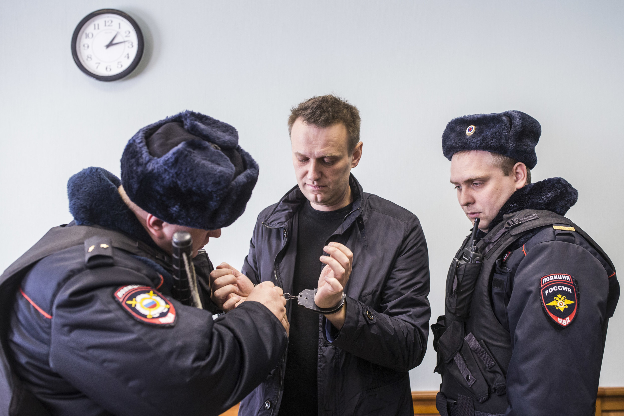 Police officers dismantle handcuffs from Alexey Navalny's hands prior to an appeal hearing after his arrest at a rally in Moscow, Russia