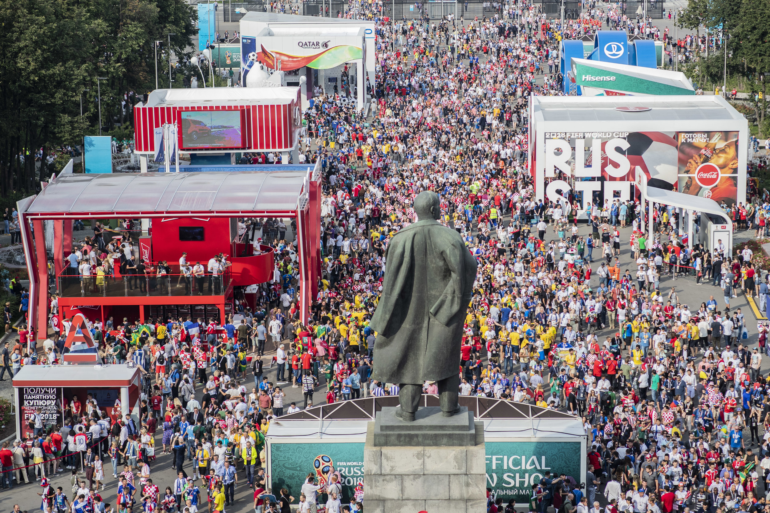 Fans of all nations enter Luzhniki stadium passing by Lenin's statue and an alley filled with sponsors' pavilions in Moscow
