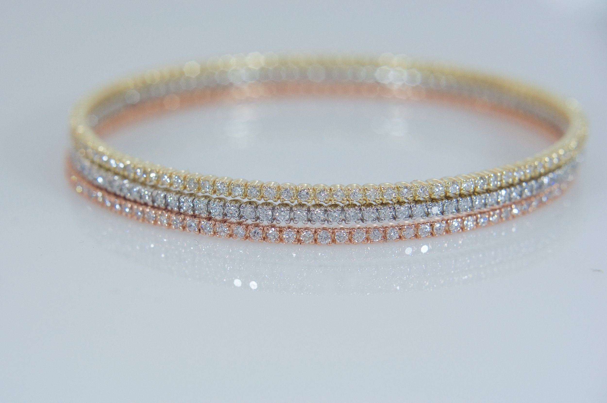 Three diamond eternity bangles in yellow, white, and rose gold